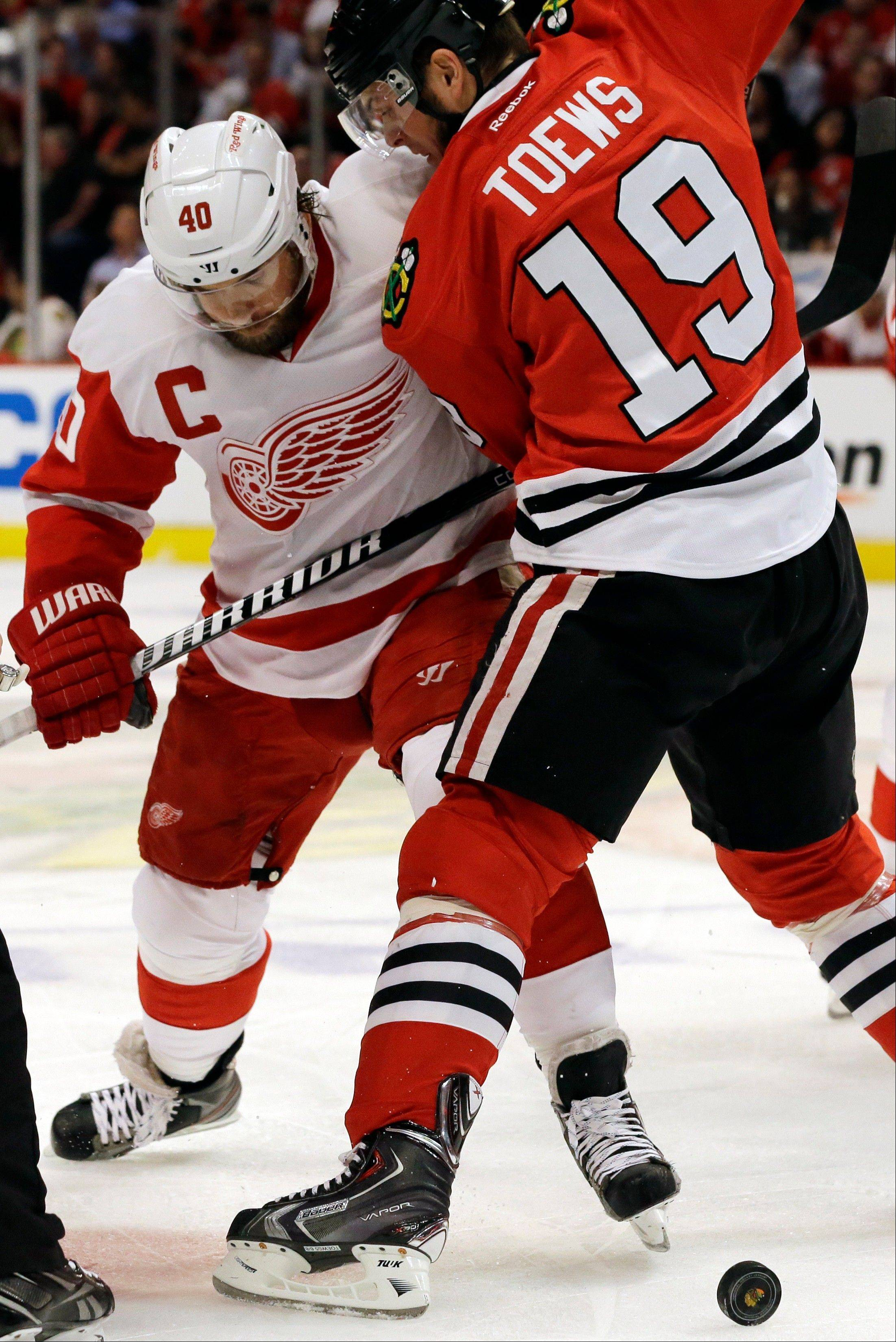 Detroit Red Wings' Henrik Zetterberg (40) battles for the puck against Chicago Blackhawks' Jonathan Toews (19) during the first period of Game 1 of an NHL hockey playoffs Western Conference semifinal in Chicago, Wednesday, May 15, 2013.