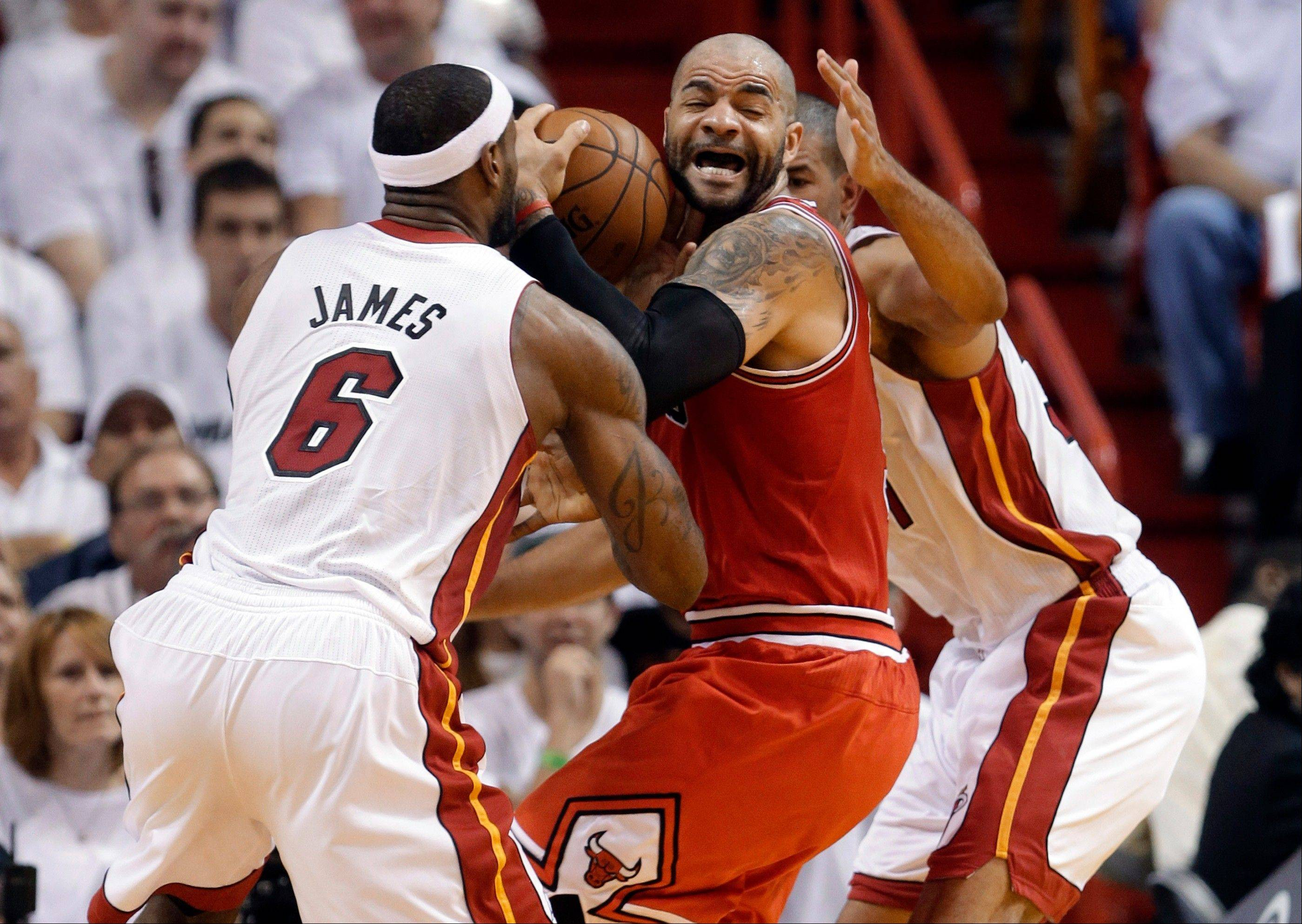 Chicago Bulls' Carlos Boozer, center, works the ball between Miami Heat's LeBron James (6) and Shane Battier, right, as he attempts to shoot during the first half of Game 5 of an NBA basketball Eastern Conference semifinal, Wednesday, May 15, 2013, in Miami.