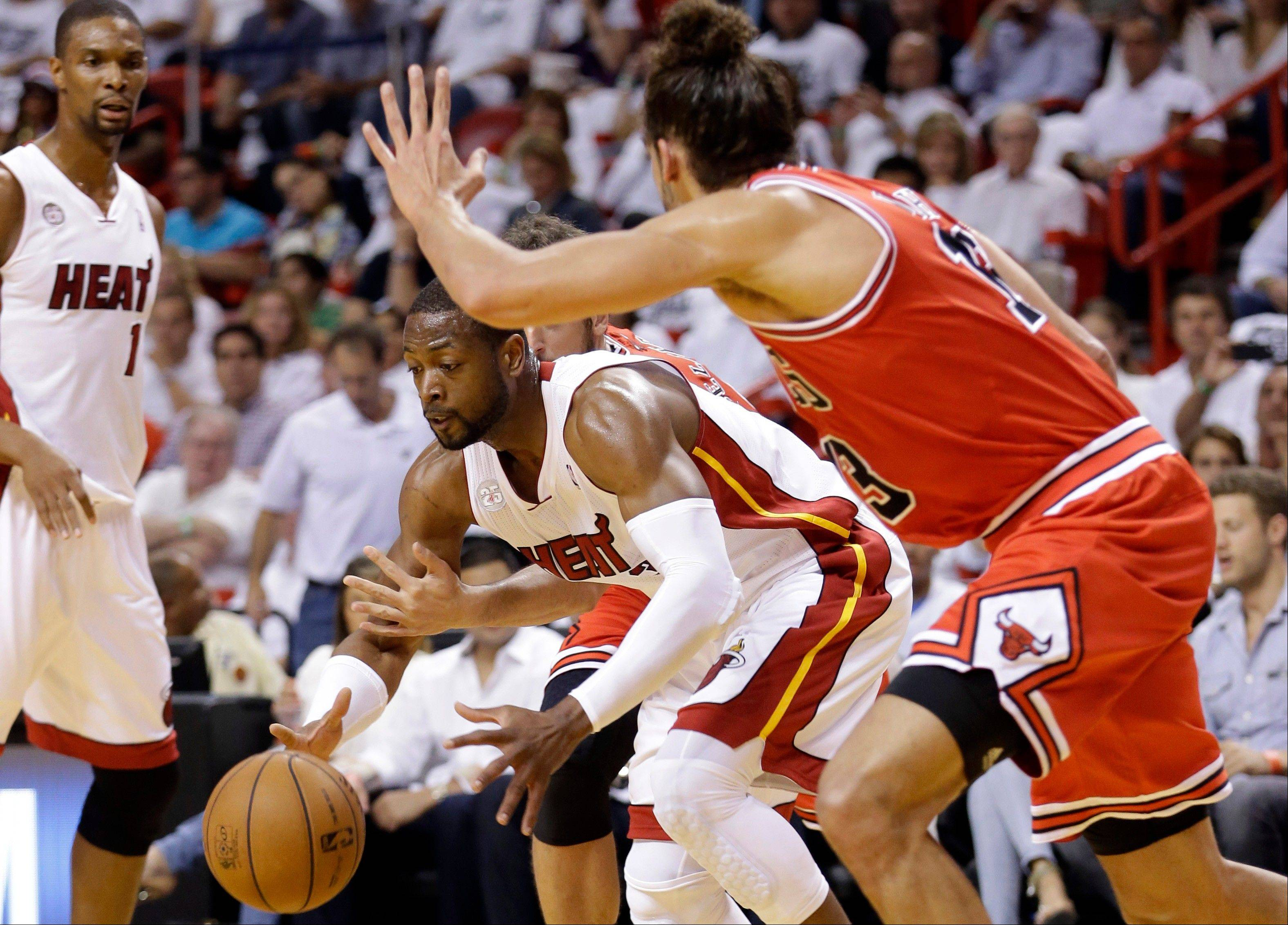 Miami Heat's Dwyane Wade, center, is defended by Chicago Bulls' Joakim Noah, right, during the first half of Game 5 of an NBA basketball playoffs Eastern Conference semifinal, Wednesday, May 15, 2013, in Miami.