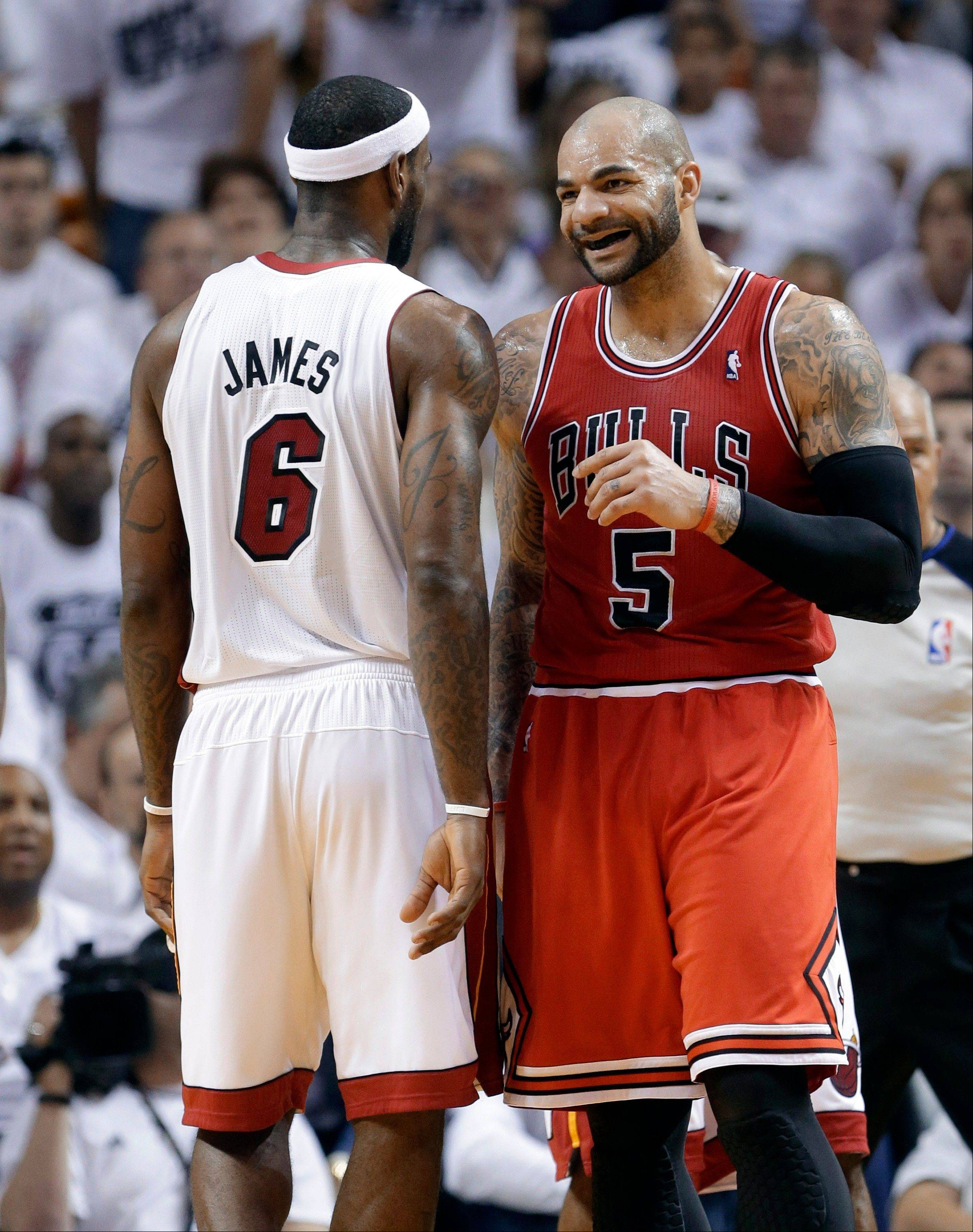 Miami Heat's LeBron James (6) and Chicago Bulls Carlos Boozer (5) stand on the court during the first half of Game 5 of an NBA basketball Eastern Conference semifinal, Wednesday, May 15, 2013, in Miami.