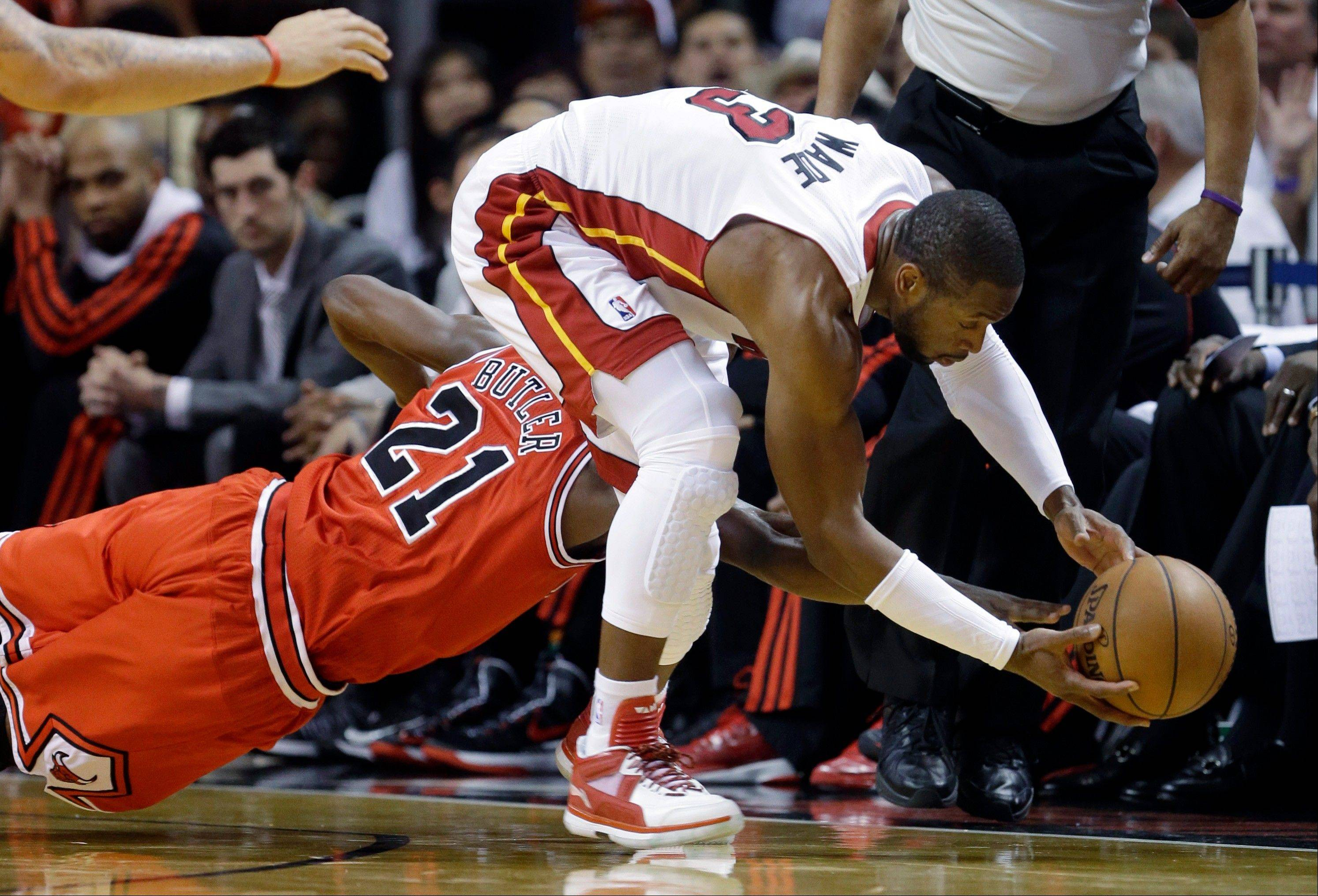 Miami Heat's Dwyane Wade (3) and Chicago Bulls' Jimmy Butler (21) go for a loose ball during the first half of Game 5 of an NBA basketball Eastern Conference semifinal, Wednesday, May 15, 2013, in Miami.