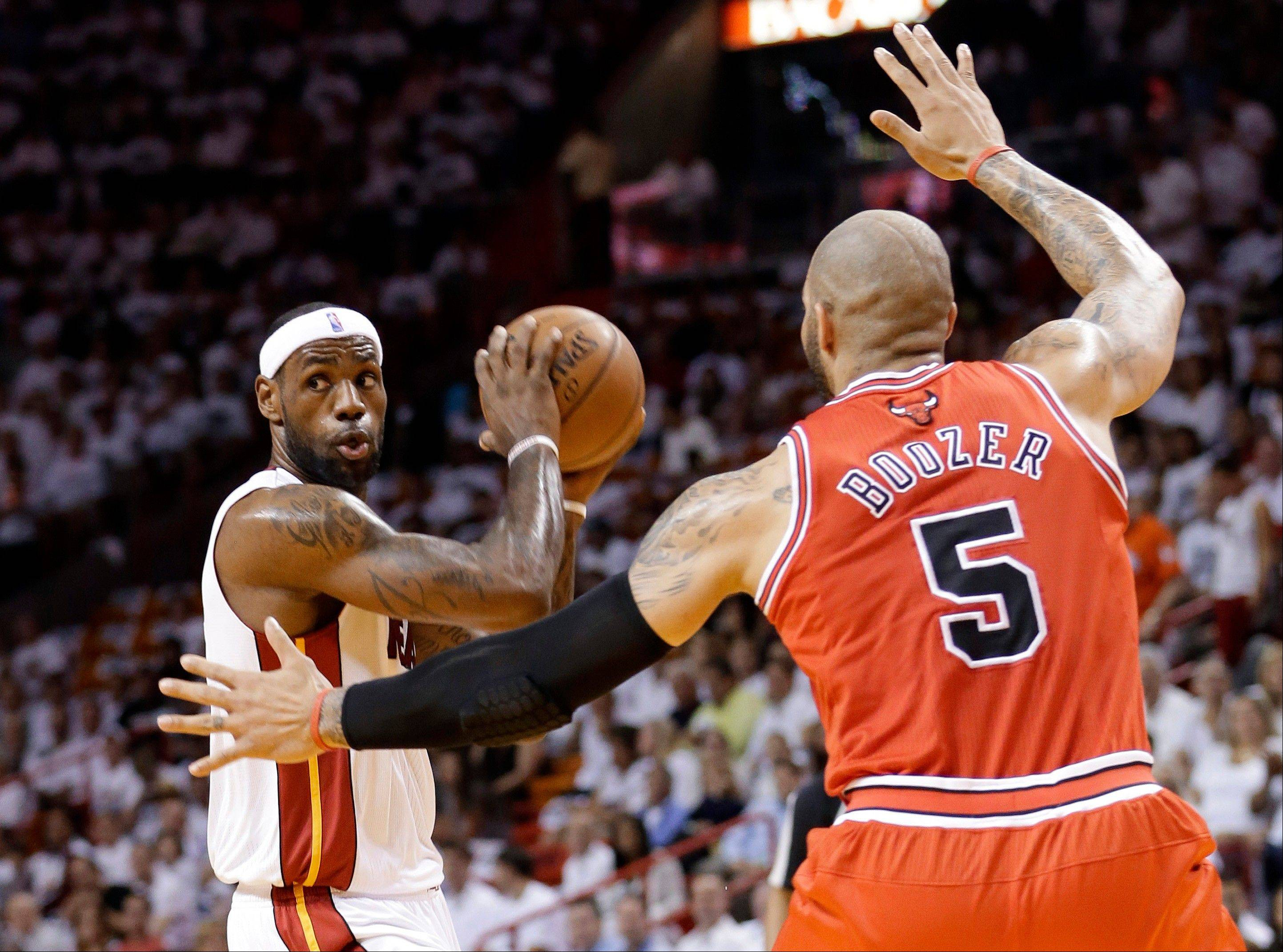 Miami Heat's LeBron James, left, looks to pass as Chicago Bulls' Carlos Boozer (5) defends during the first half of Game 5 of an NBA basketball Eastern Conference semifinal, Wednesday, May 15, 2013, in Miami.