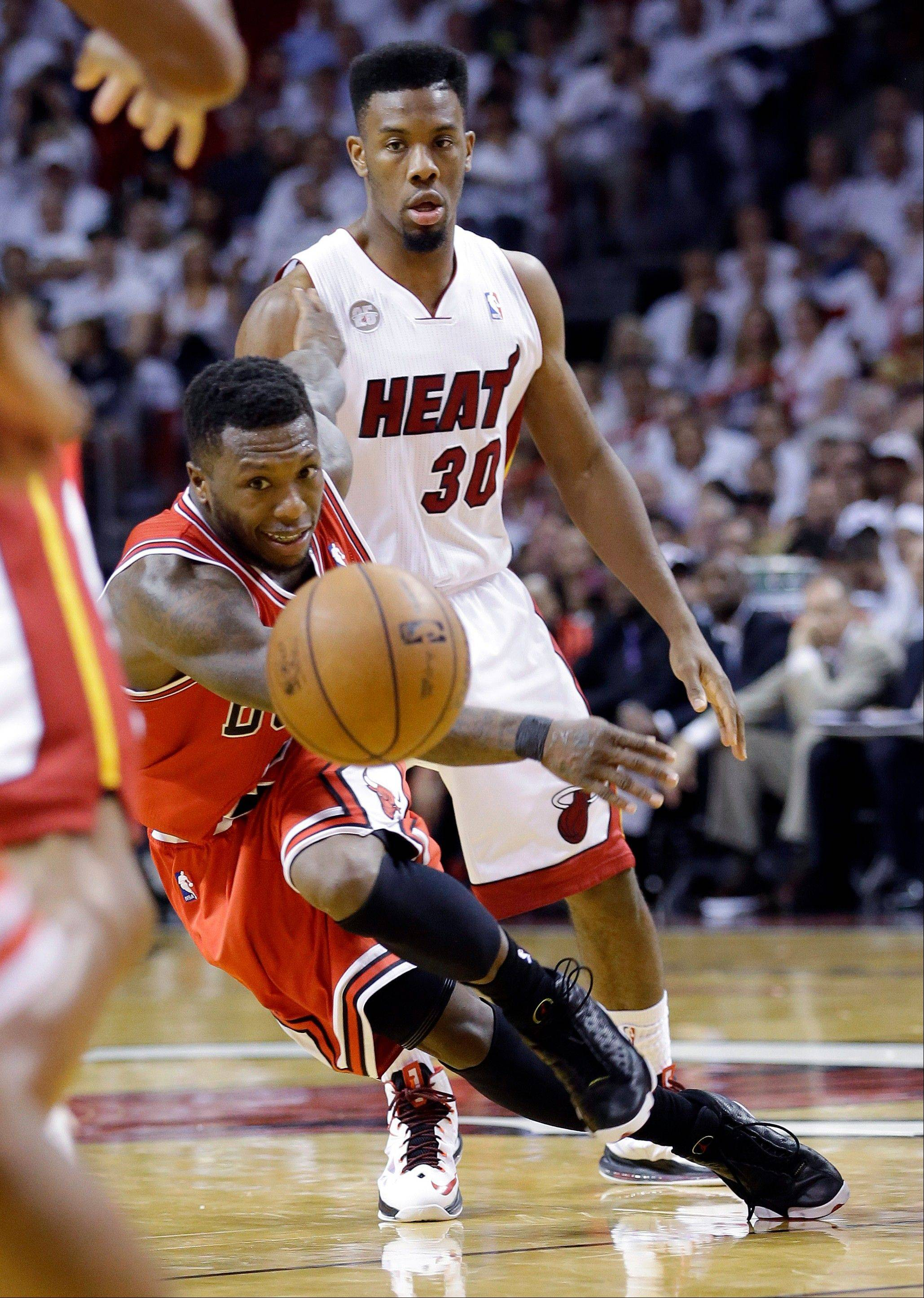 Chicago Bulls' Nate Robinson passes the ball as Miami Heat's Norris Cole (30) watches during the second half of Game 5 of an NBA basketball Eastern Conference semifinal, Wednesday, May 15, 2013, in Miami.