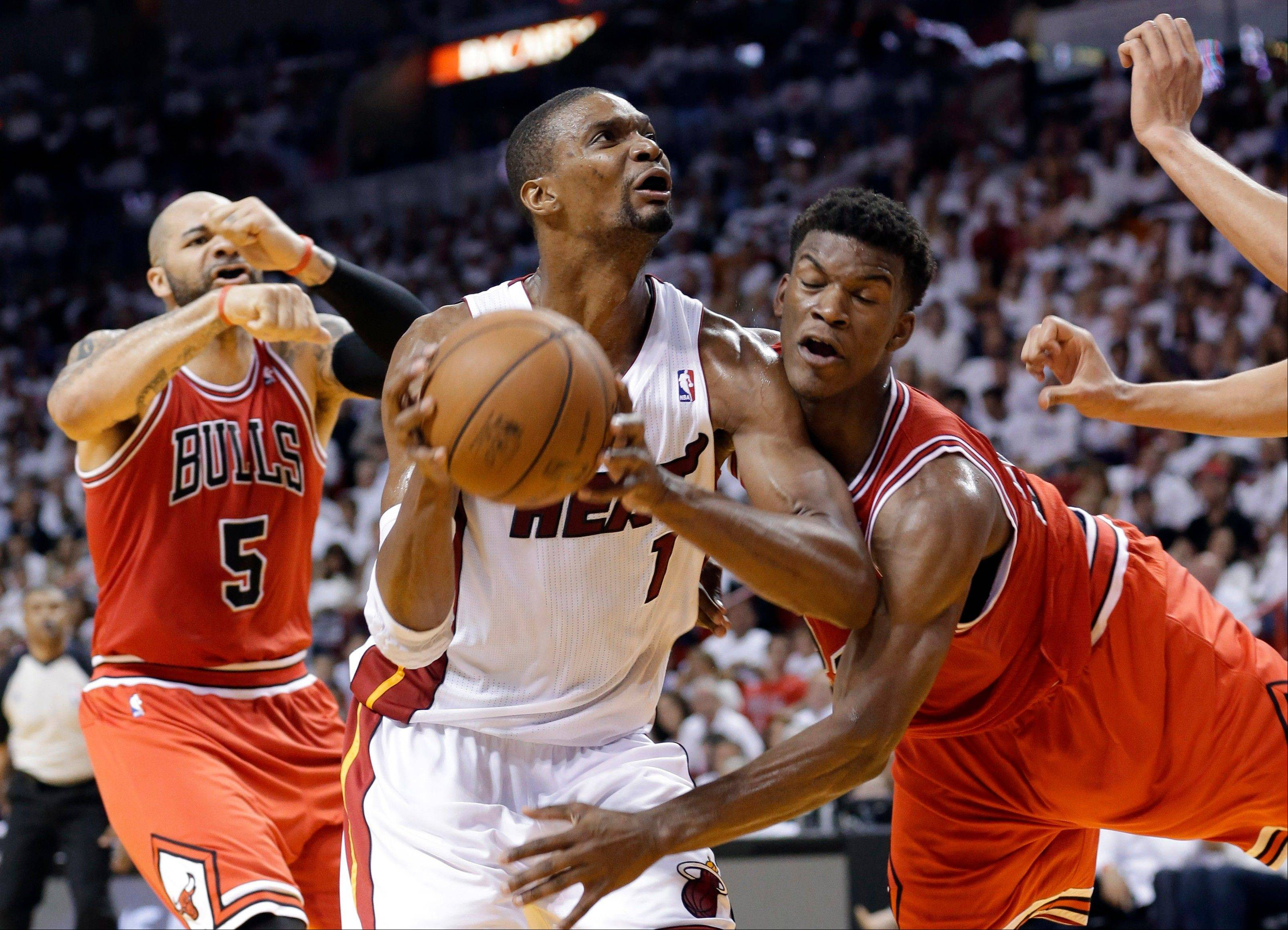 Miami Heat's Chris Bosh (1) drives to the basket as Chicago Bulls' Jimmy Butler, right, defends during the first half of Game 5 of an NBA basketball Eastern Conference semifinal, Wednesday, May 15, 2013 in Miami. At left is Bulls' Carlos Boozer.