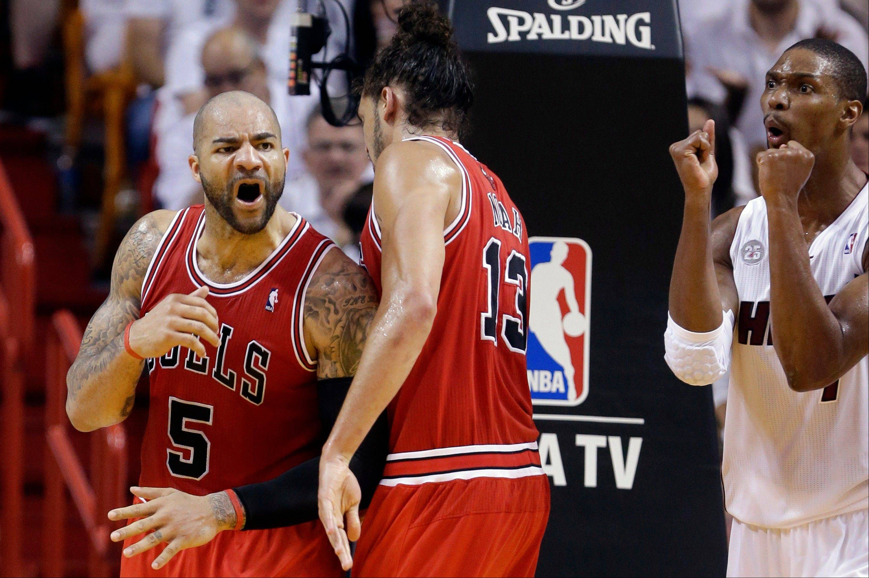 Chicago Bulls' Carlos Boozer (5) reacts after Miami Heat's Chris Bosh, right, was called for a foul during the first half of Game 5 of an NBA basketball Eastern Conference semifinal, Wednesday, May 15, 2013, in Miami. At center is Bulls' Joakim Noah.