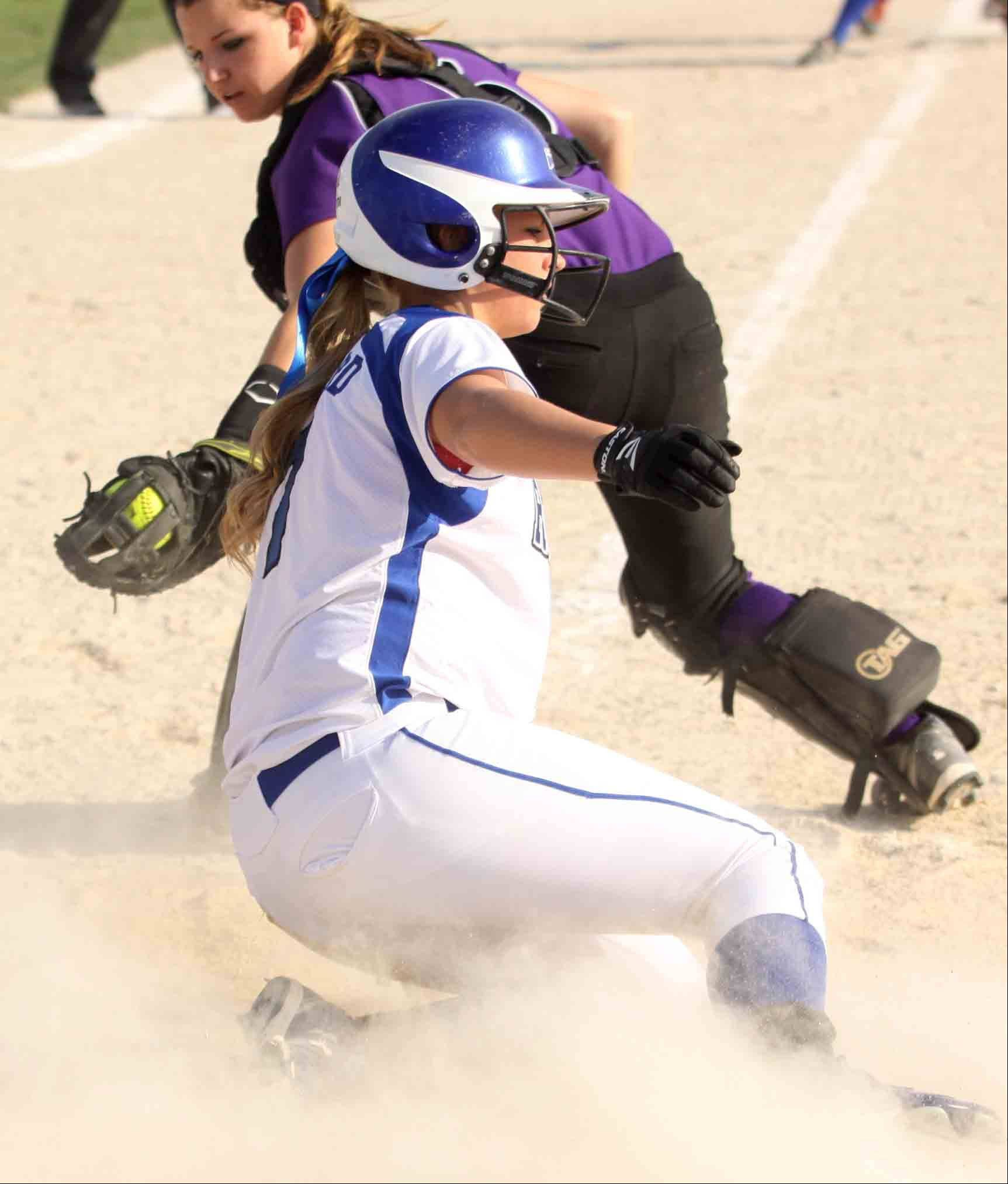 Burlington Central's Brooke Gaylord slides safely into home as Hampshire catcher Sara Finn looks back to make a tag Wednesday at Burlington.