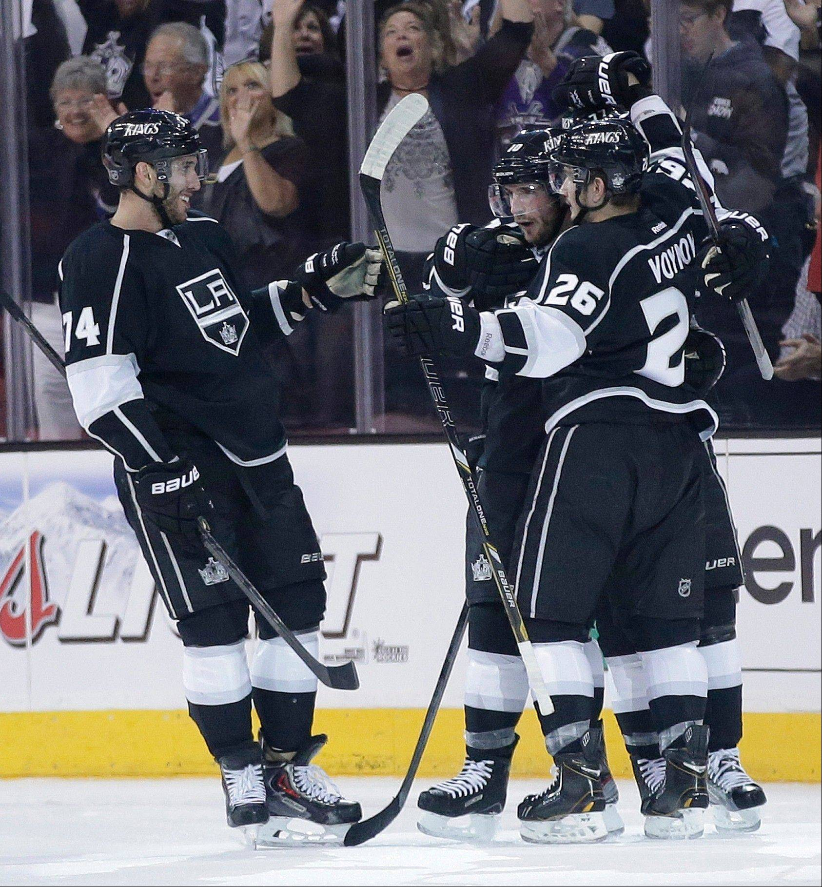 Los Angeles Kings' Slava Voynov (26) celebrates his first-period goal against the San Jose Sharks with teammates Dwight King, left, and Jeff Carter in Game 1 of a second-round NHL hockey Stanley Cup playoff series, in Los Angeles, Tuesday, May 14, 2013.