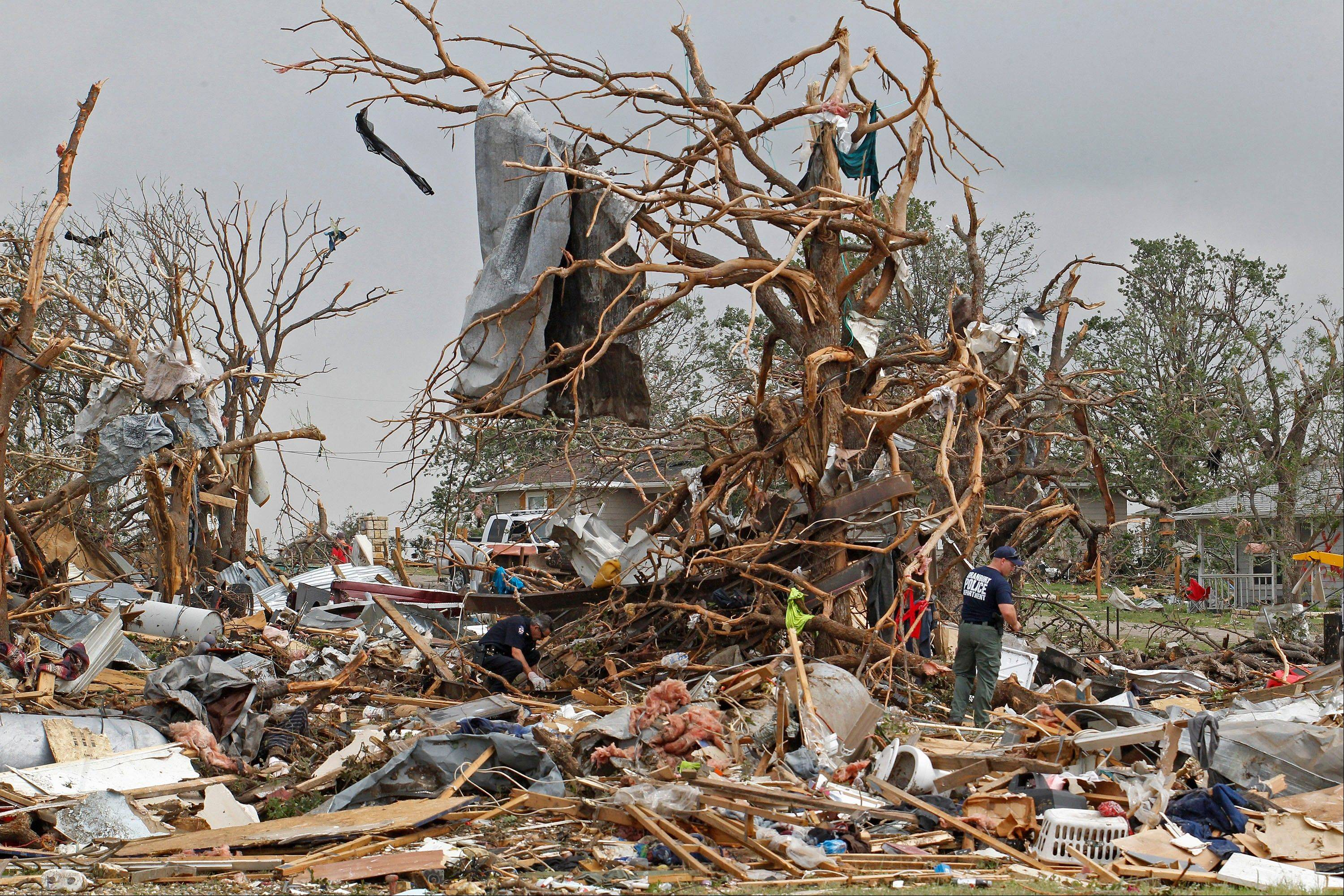 Crushed autos sit amid the rubble of destroyed homes as emergency personnel continue search efforts to locate unaccounted for people in the Rancho Brazos neighborhood in Granbury, Texas, Thursday, May 16, 2013. A rash of tornadoes slammed into several small communities in North Texas overnight, leaving at least six people dead, dozens more injured and hundreds homeless.