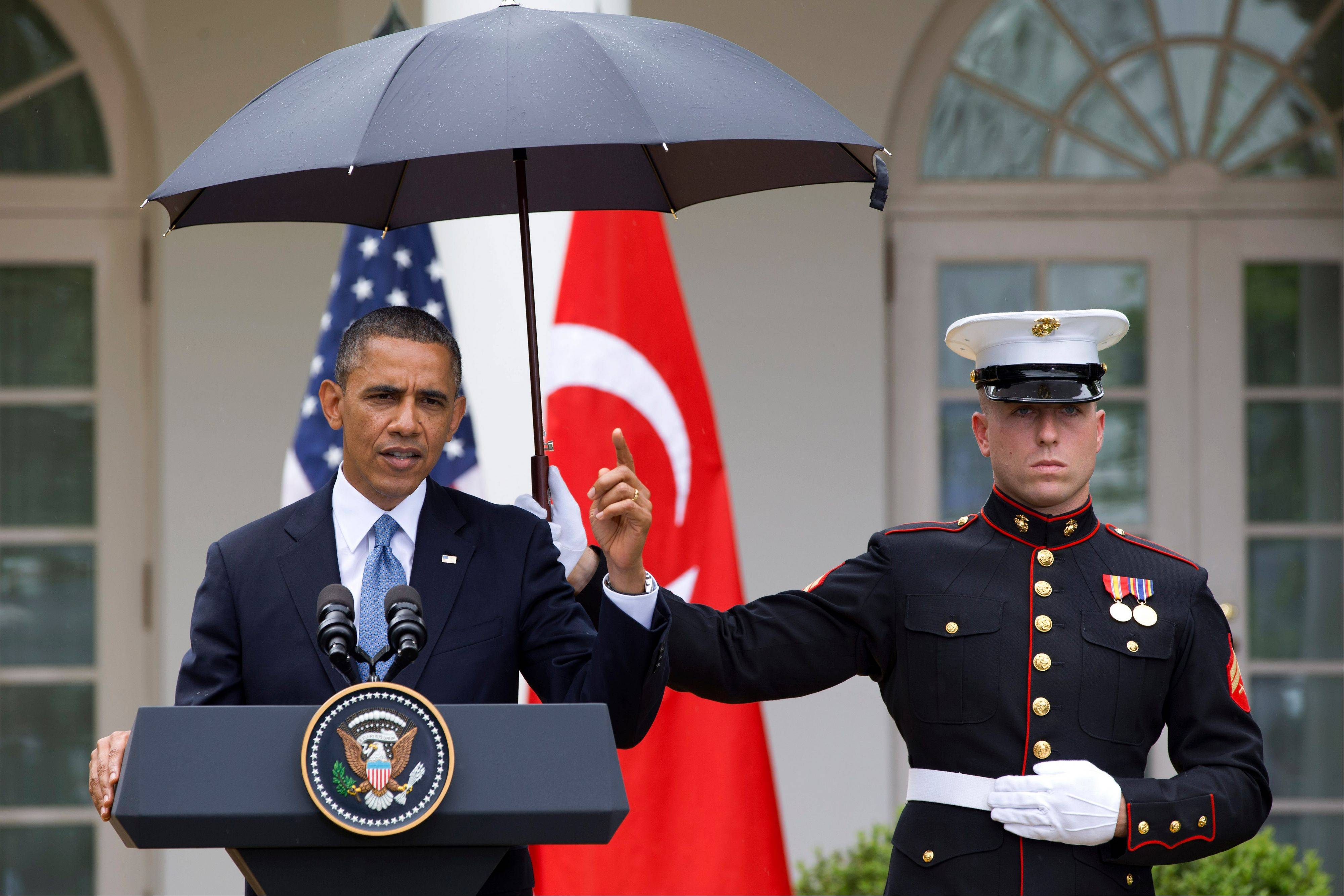 President Barack Obama speaks under an umbrella held by a Marine as a light rain falls during a news conference with Turkish Prime Minister Recep Tayyip Erdogan Thursday in the Rose Garden of the White House. Obama also addressed the controversy over IRS targeting specific organizations .