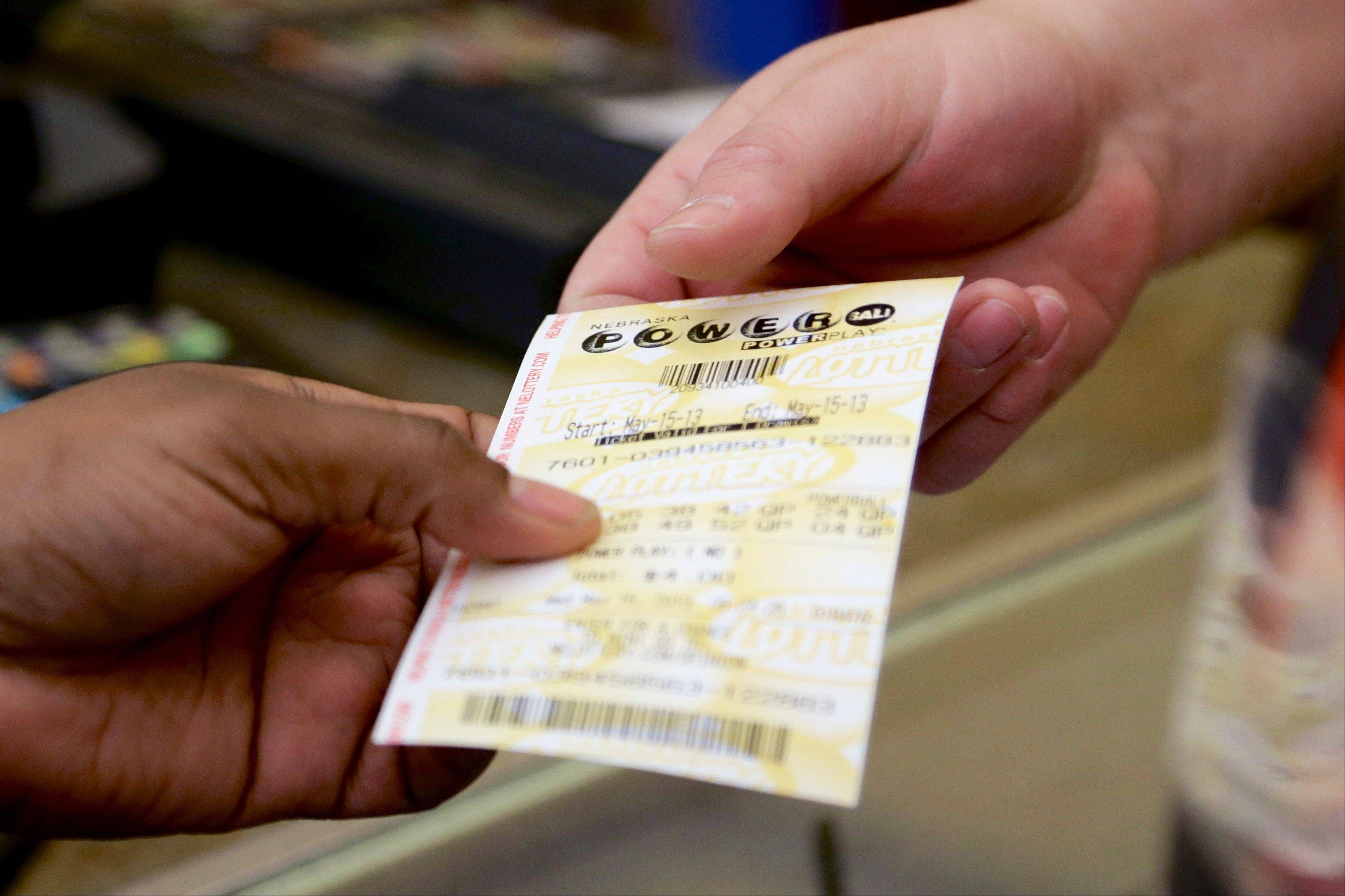 A customer receives her Powerball ticket Wednesday at a Baker's supermarket in Omaha, Neb.