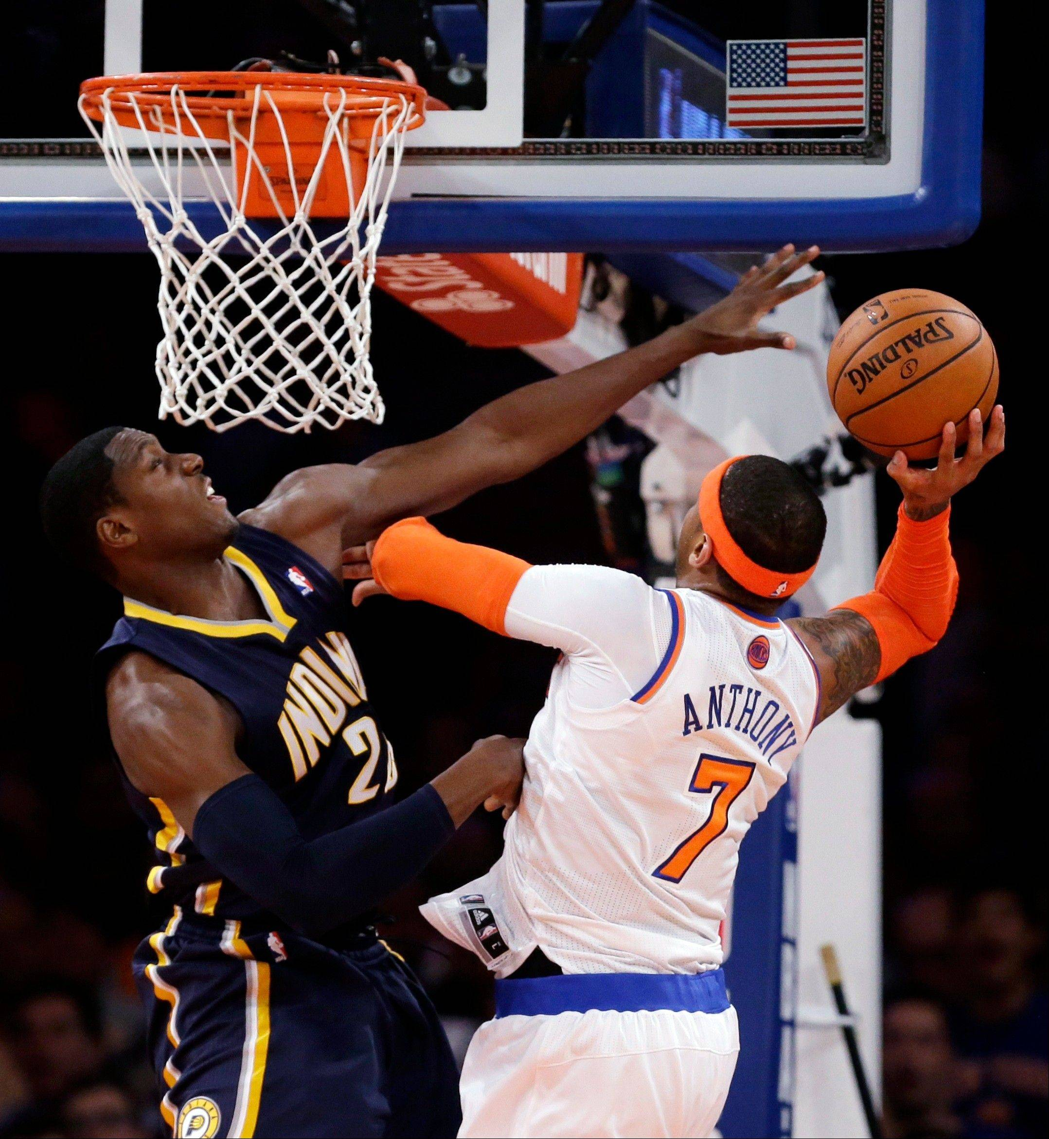 New York Knicks' Carmelo Anthony, right, goes up for a shot against Indiana Pacers' Paul George in the first half of Game 5 of an Eastern Conference semifinal in the NBA basketball playoffs, at Madison Square Garden in New York, Thursday, May 16, 2013. (AP Photo/Julio Cortez)