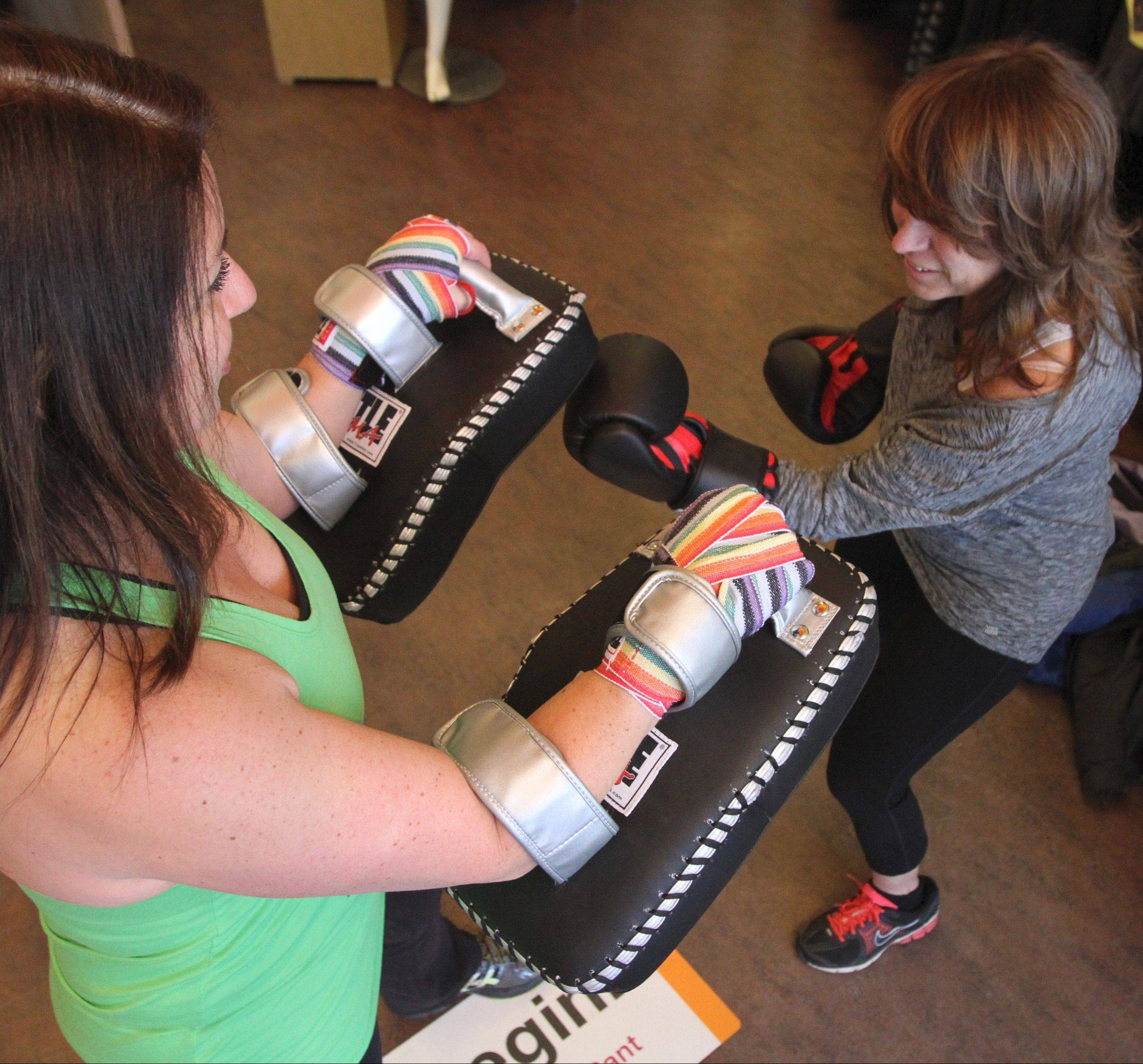 "Sue Turco, right, with Wood Dale Park District Fittest Loser Community Challenge team ""Warriors,"" during a power workout with Title Boxing Club of Lake Zurich co-owner Lisa Somlo at the Lucy store at Deer Park Town Center."
