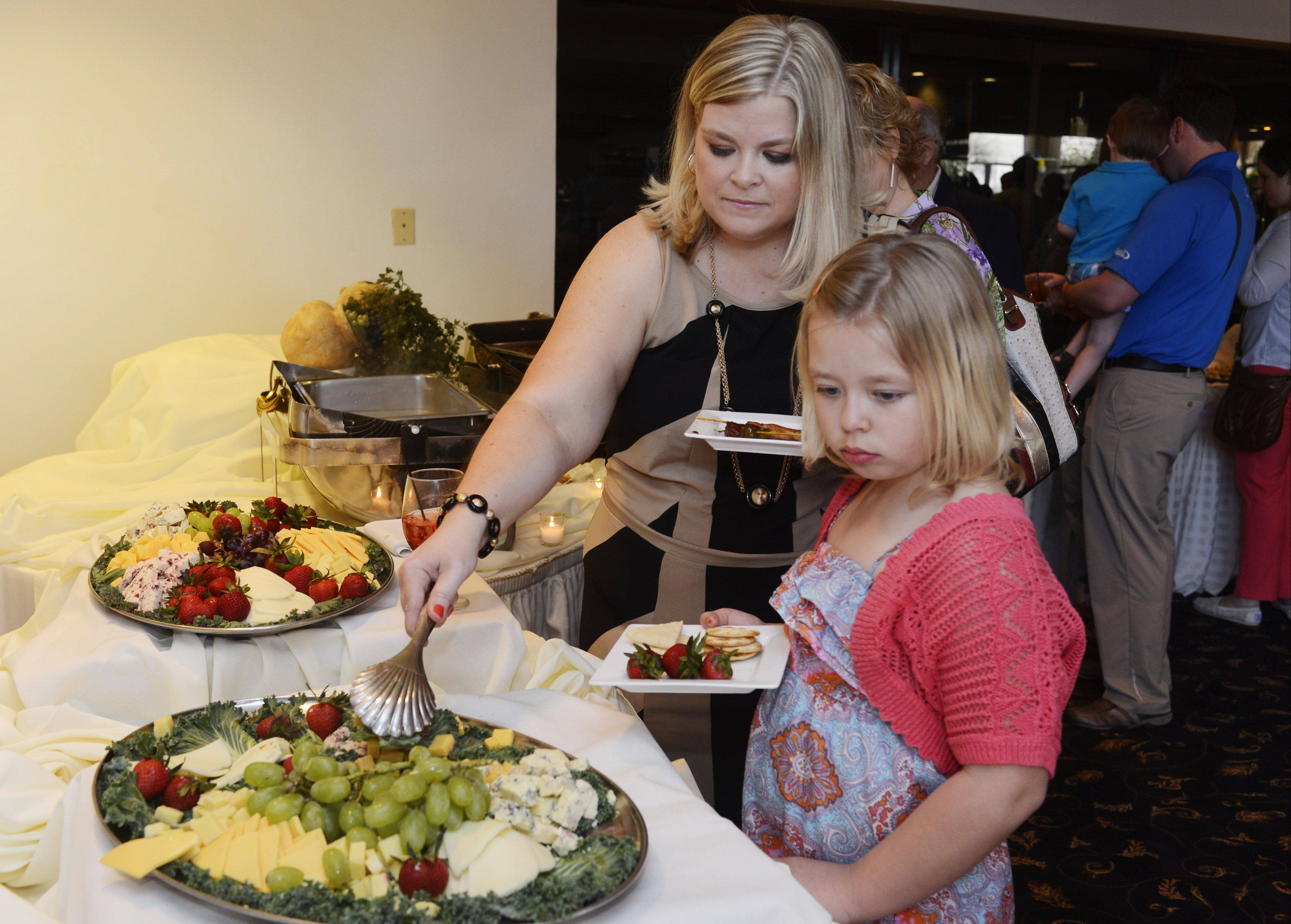 Contestant Megan McCarthy-Cook and her daughter, Molly, 8, select items from the buffet during the Fittest Loser celebration at Victoria in the Park in Mount Prospect.