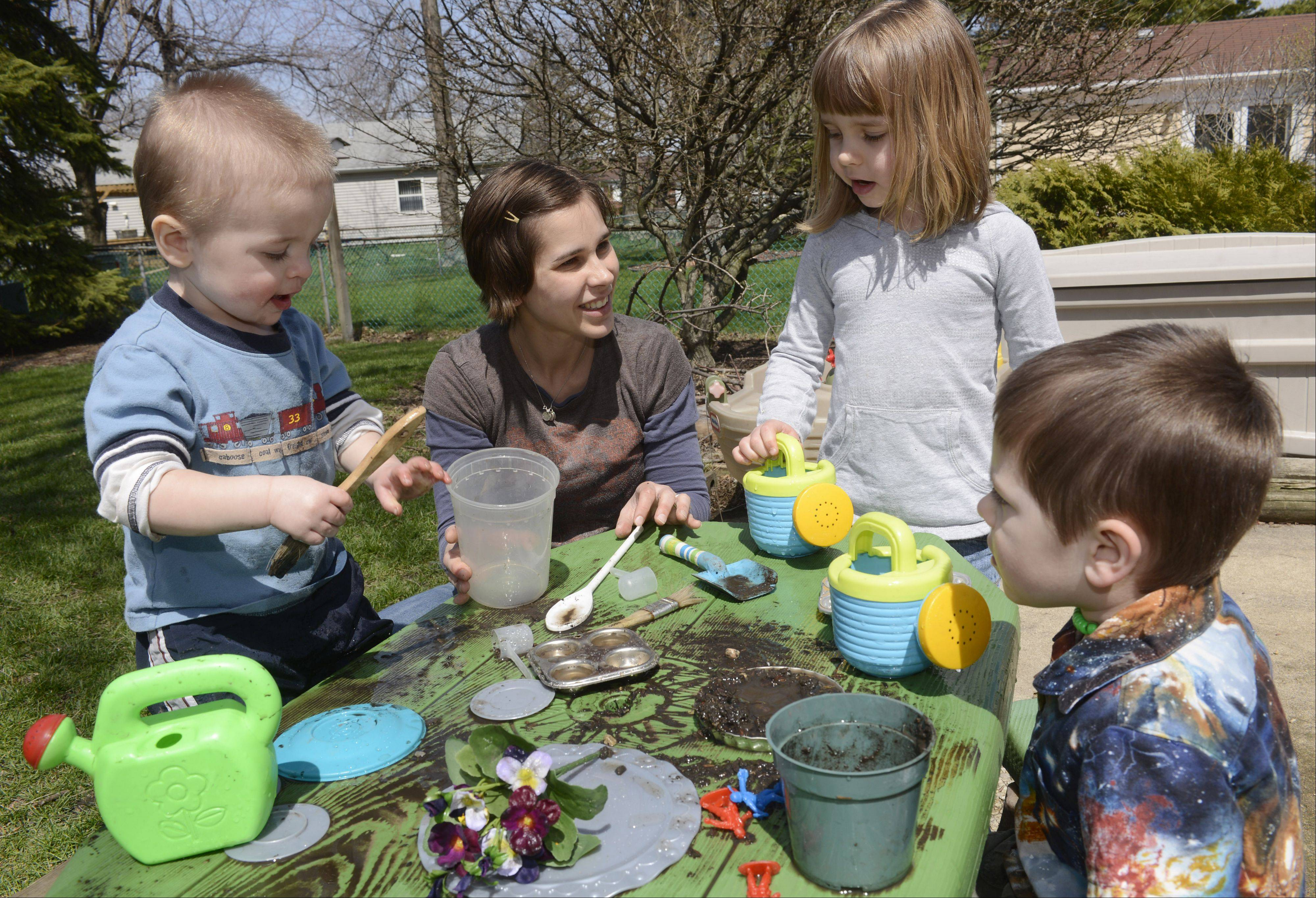 Left to right, Benjamin Anderson, 1, his mom, Becki, sister Lily, 4, and brother Justin, 3, make mud pies in the back yard of their Schaumburg home.