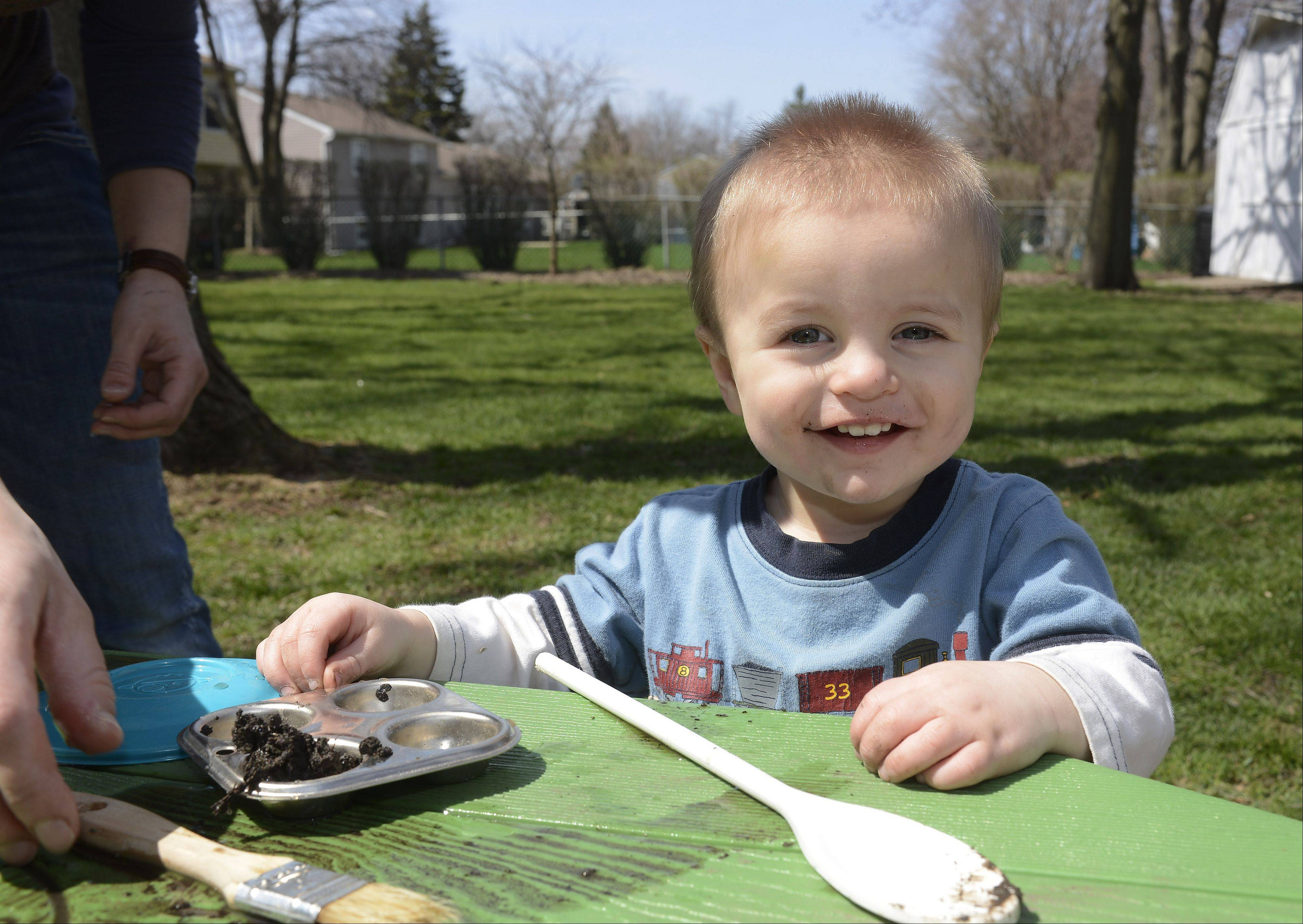 Benjamin Anderson, 1, plays with mud in a baking tin at his parent's Schaumburg home.