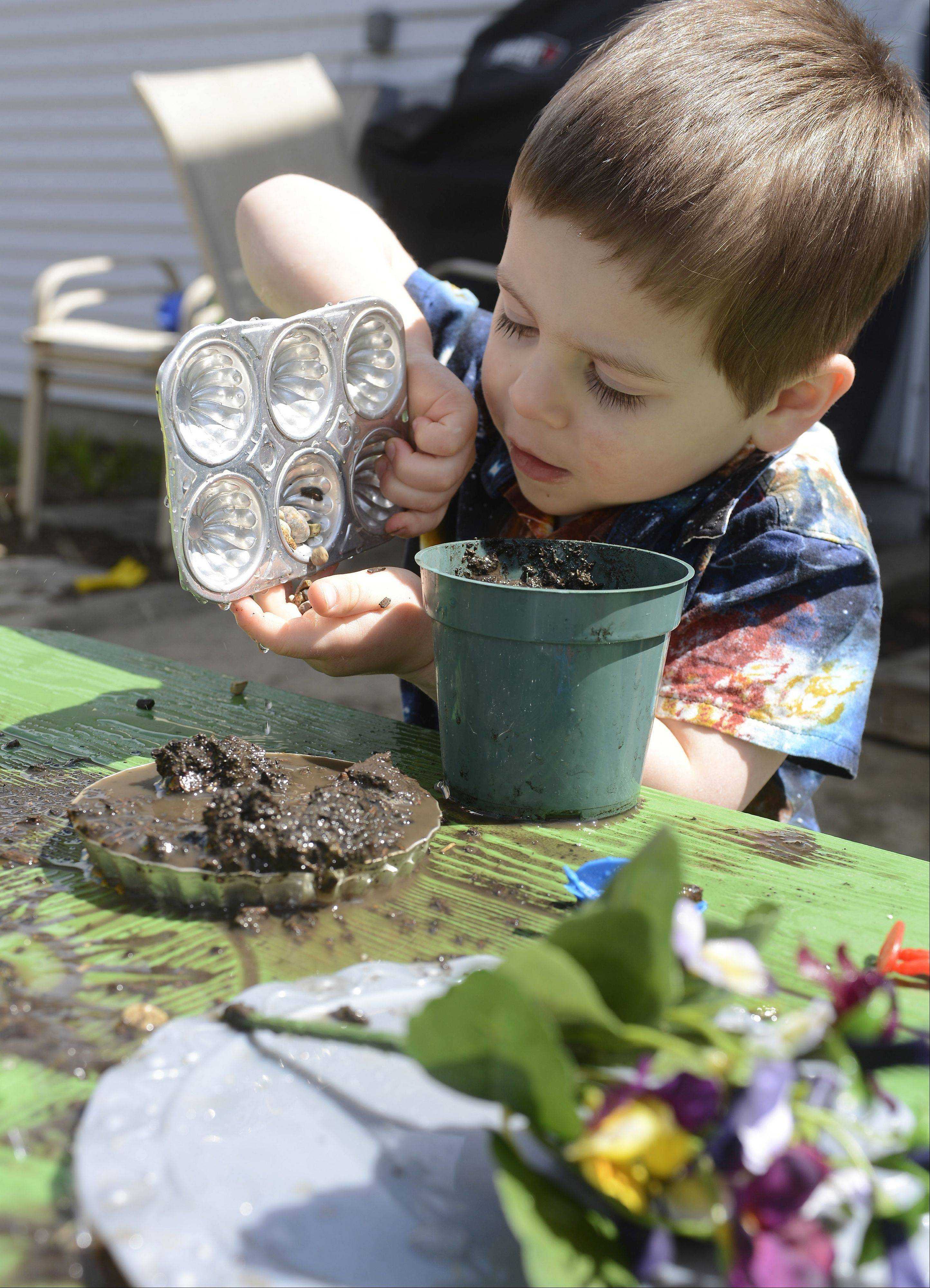 Justin Anderson, 3, uses small stones for sprinkles while making a mud pie.