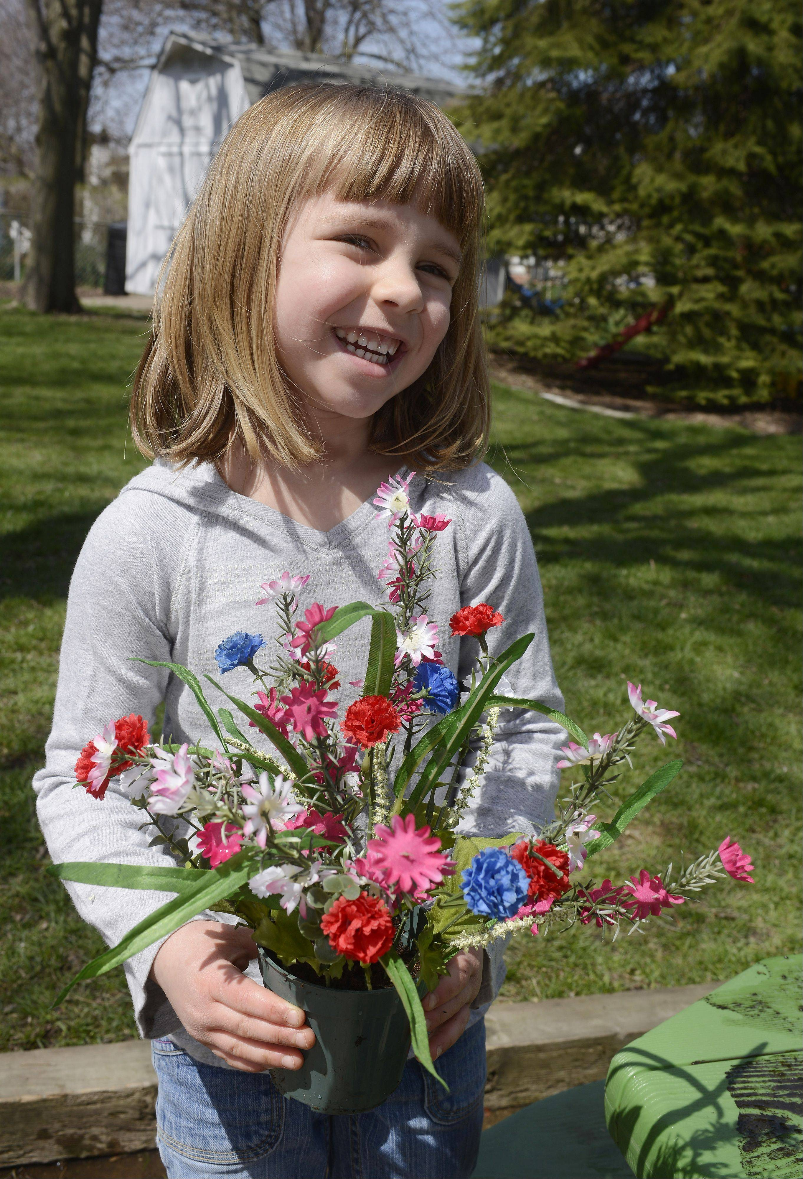 Lily Anderson, 4, smiles after placing artificial flowers in a pot of soil.
