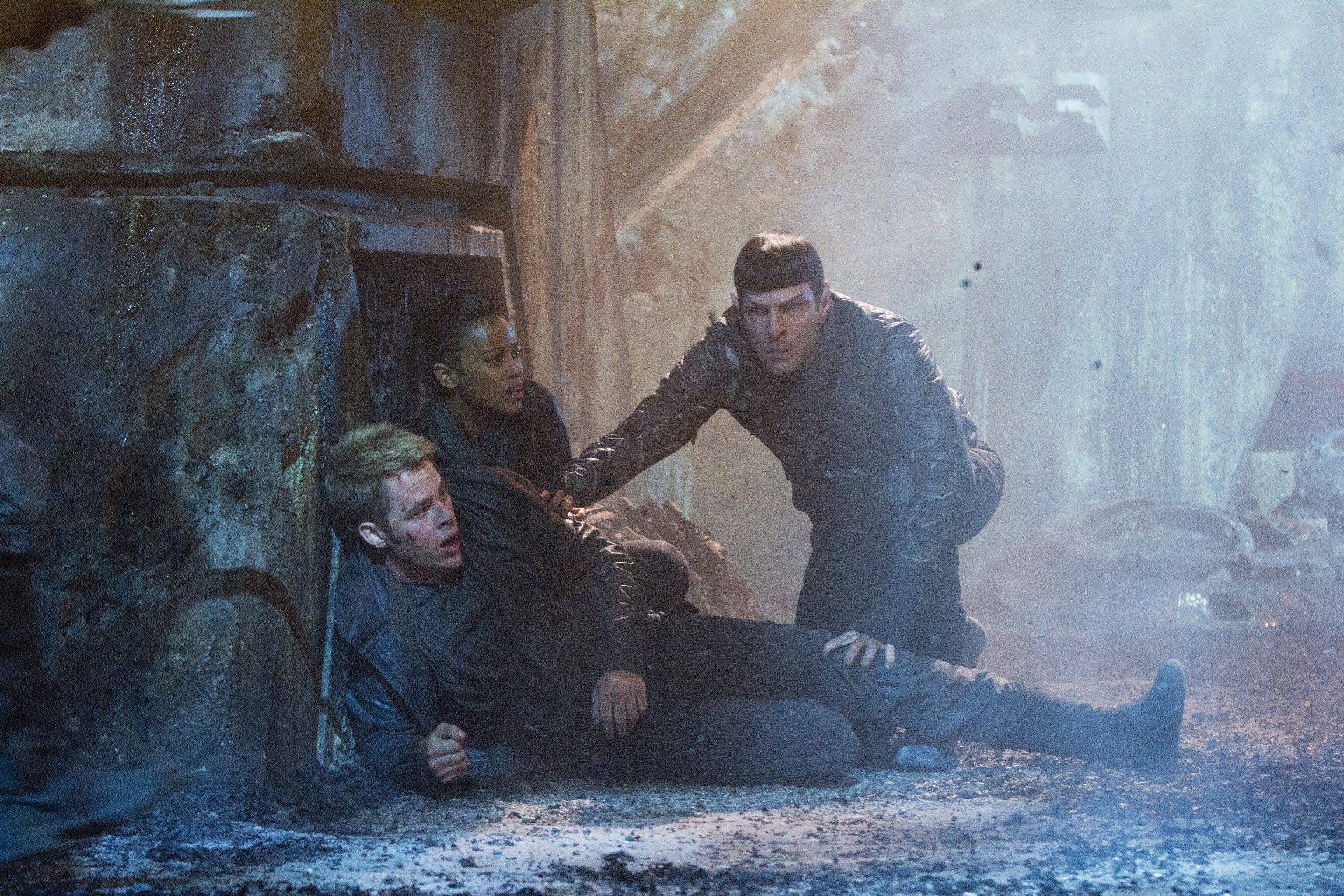 "Capt. Kirk (Chris Pine) receives assistance from Uhura (Zoe Saldana) and Spock (Zachary Quinto) in J.J. Abrams' reboot sequel ""Star Trek Into Darkness."""