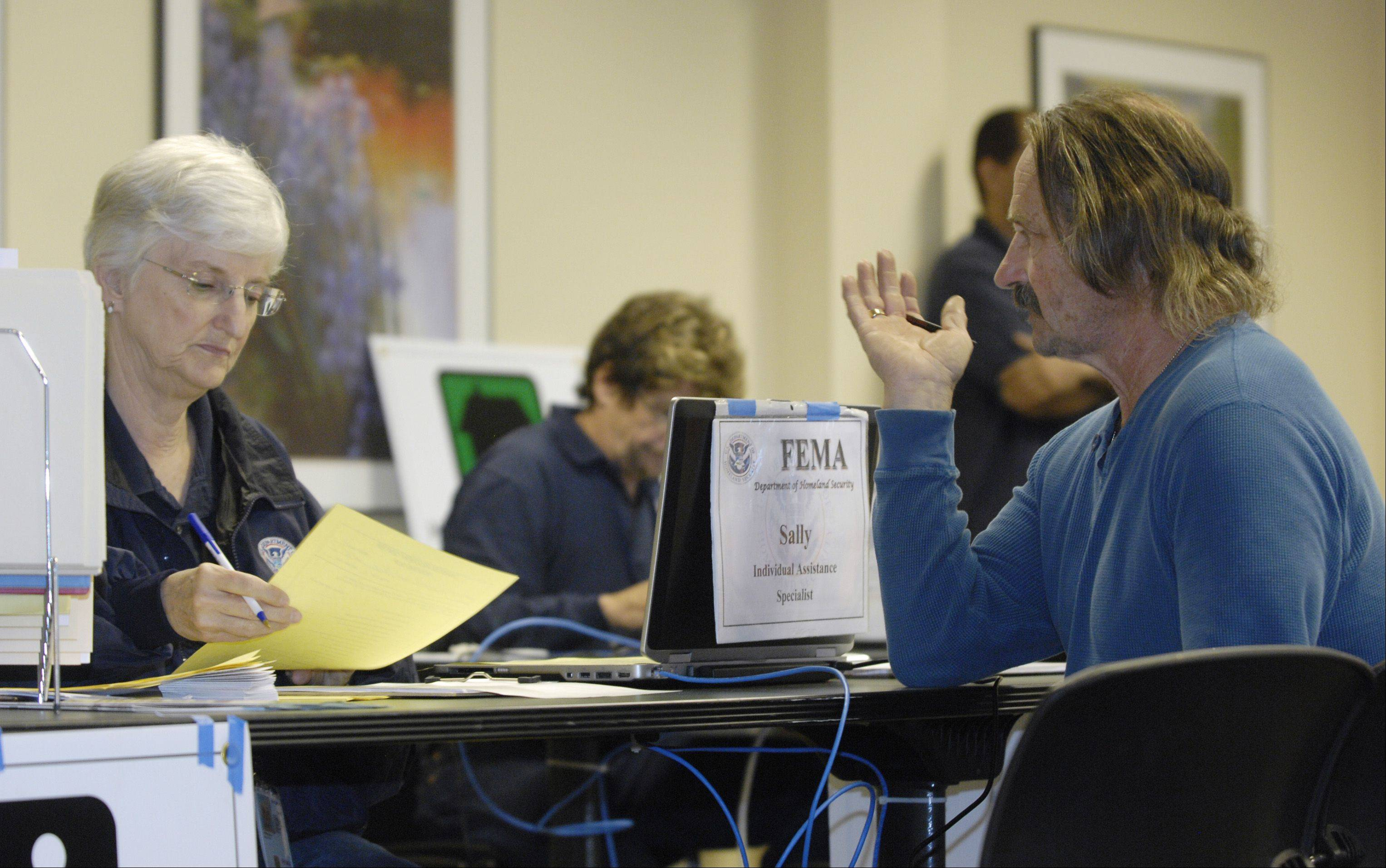 FEMA employee Sally Stribling talks Thursday with flood victim Robert DeVincentis of Lisle in the newly opened FEMA Disaster Recovery Center in the Lisle Police Department. Officials say the center will remain open until residents and business owners no longer need it.