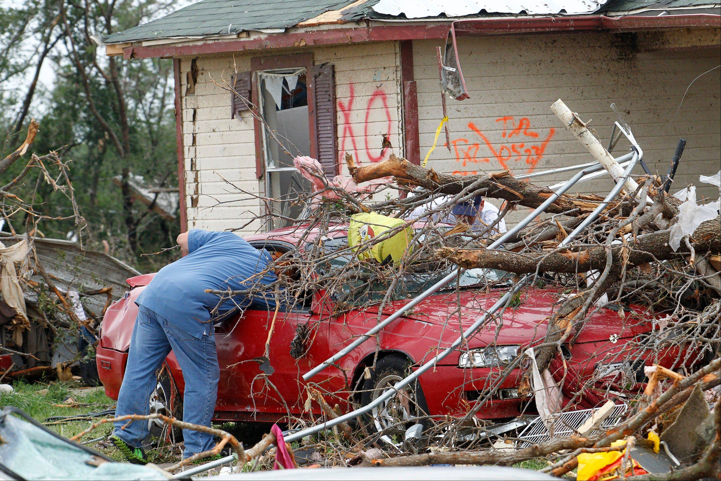 Crushed autos sit amid the rubble as emergency personnel continue search efforts to locate unaccounted for people in the Rancho Brazos neighborhood in Granbury, Texas, Thursday, May 16, 2013. A rash of tornadoes slammed into several small communities in North Texas overnight, leaving at least six people dead, dozens more injured and hundreds homeless.