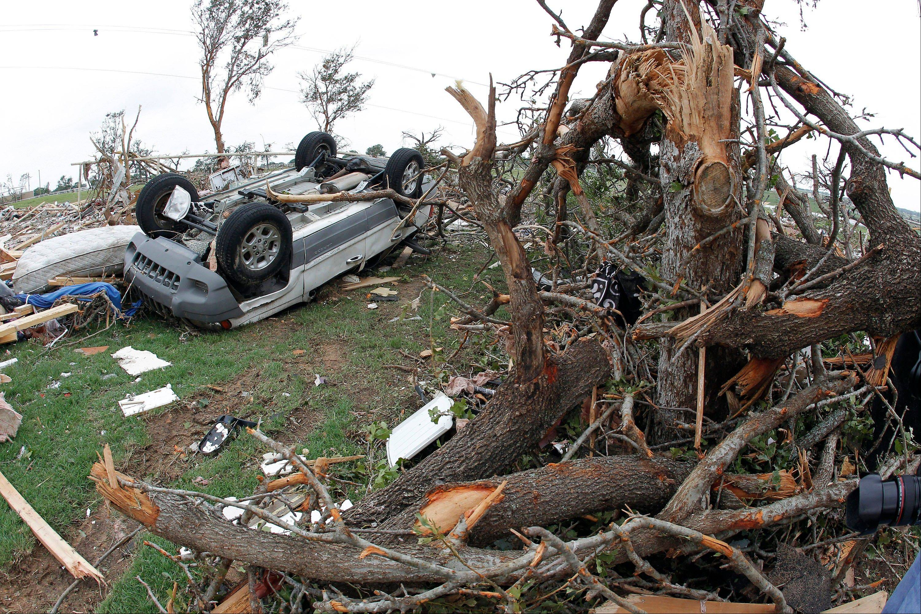 A toppled car lies next to and crushed trees in the Rancho Brazos neighborhood of Granbury, Texas on Thursday, May 16, 2013. Ten tornadoes touched down in several small communities in North Texas overnight, leaving at least six people dead, dozens injured and hundreds homeless. Emergency responders were still searching for missing people Thursday afternoon.