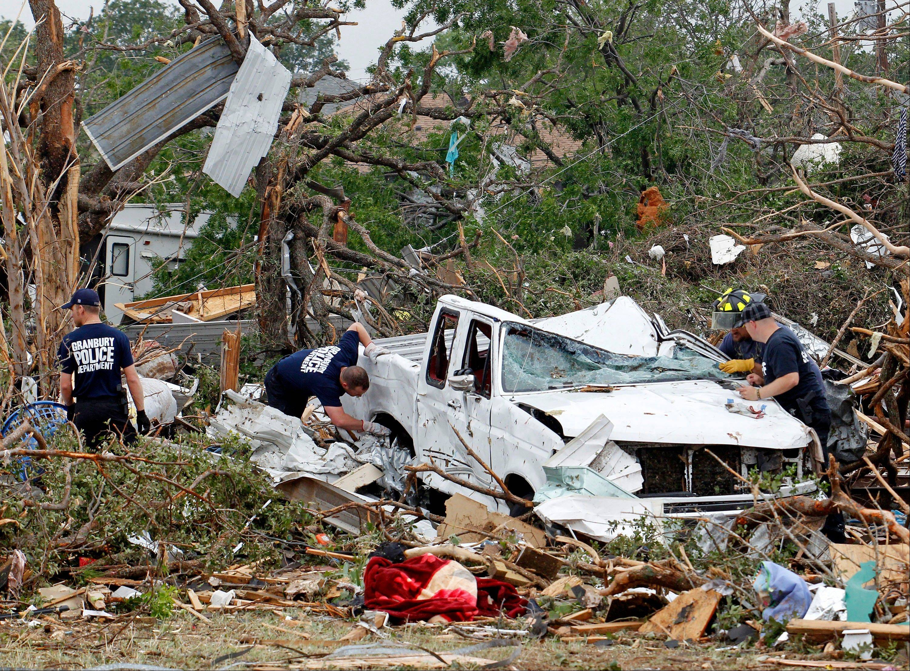 Crushed autos sit amid the rubble as emergency personnel continue search efforts to locate people in that are unaccounted for in the destroyed Rancho Brazos neighborhood of Granbury, Texas, Thursday, May 16, 2013. Ten tornadoes touched down in several small communities in North Texas overnight, leaving at least six people dead, dozens injured and hundreds homeless.