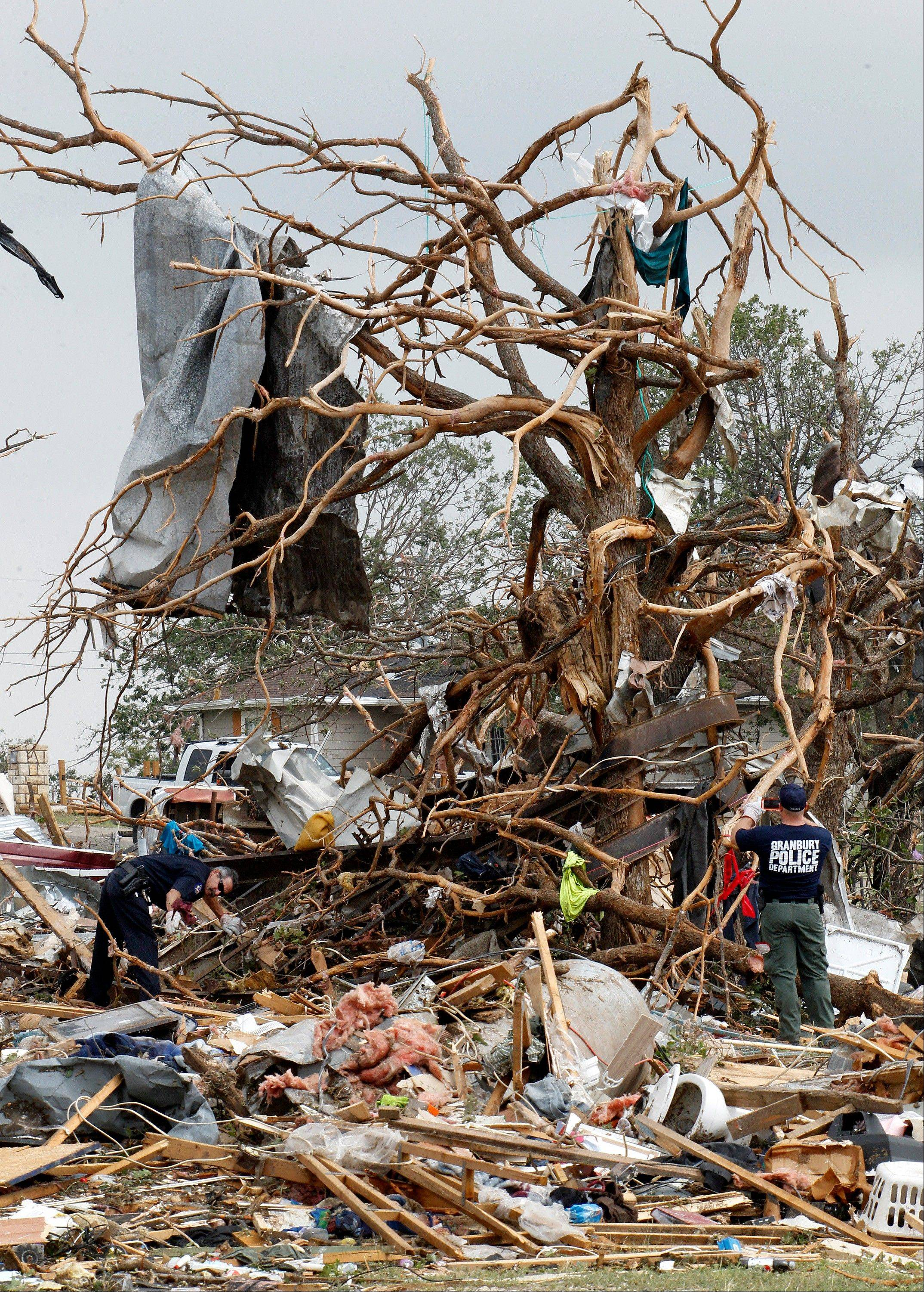 Searchers working the Rancho Brazos neighborhood in Granbury, Texas, look for unaccounted residents, Thursday, May 16, 2013. A rash of tornadoes slammed into several small communities in North Texas overnight, leaving at least six people dead, dozens more injured and hundreds homeless.