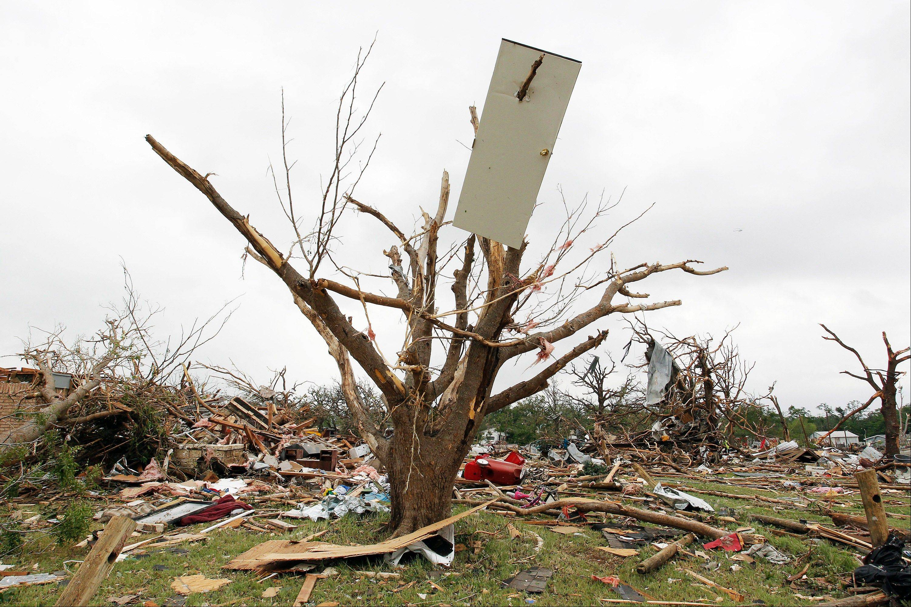 A door from a house hangs from a tree limb in the destroyed Rancho Brazos neighborhood of Granbury, Texas, Thursday, May 16, 2013. Ten tornadoes touched down in several small communities in North Texas overnight, leaving at least six people dead, dozens injured and hundreds homeless. Emergency responders were still searching for missing people Thursday afternoon.