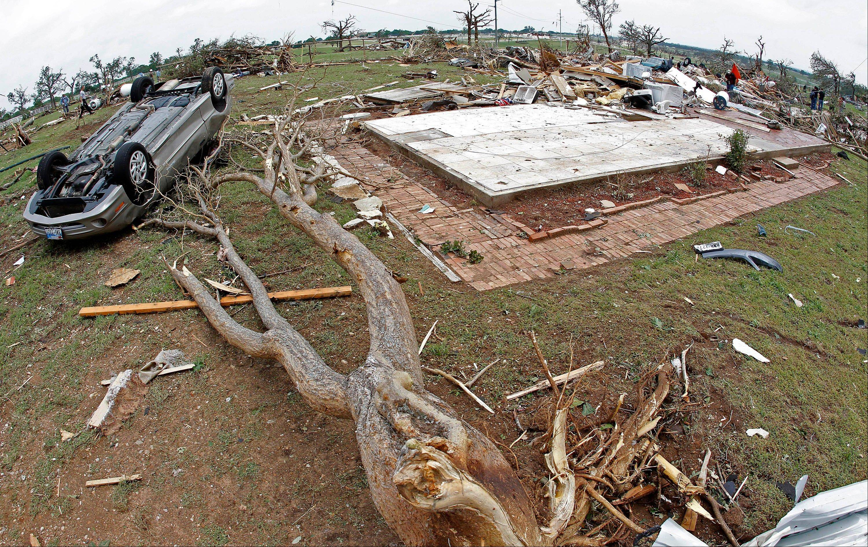 A toppled car and crushed trees lay next to the slab of a house swept off its foundation in the destroyed Rancho Brazos neighborhood of Granbury, Texas, Thursday, May 16, 2013. Ten tornadoes touched down in several small communities in North Texas overnight, leaving at least six people dead, dozens injured and hundreds homeless. Emergency responders were still searching for missing people Thursday afternoon.