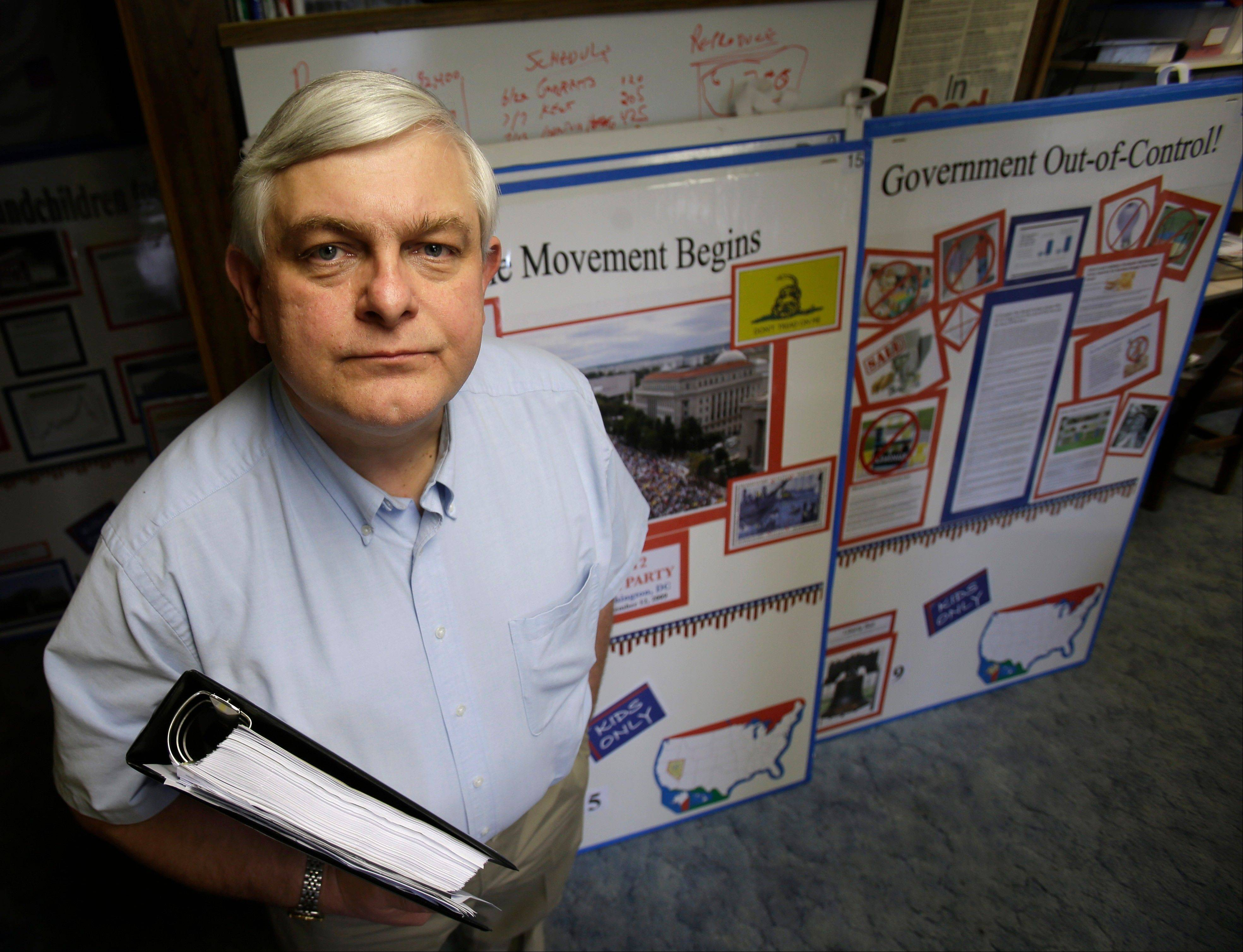 Tom Zawistowki, founder of the nonprofit Ohio Liberty Coalition, one of the region's largest groups affiliated with the national tea party movement, poses with a binder of documents he gave to the IRS, in Kent, Ohio.