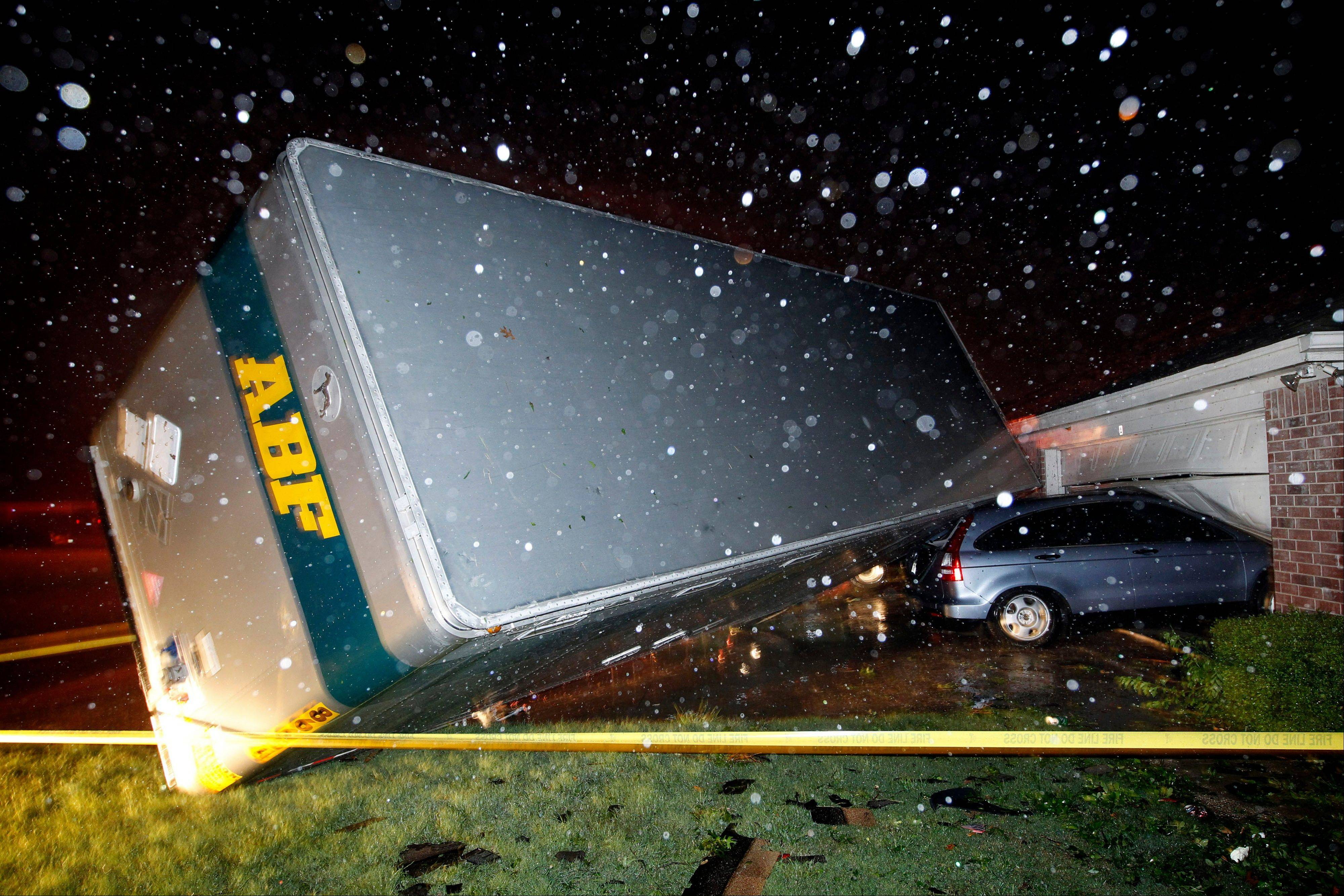 A trucking company trailer landed on a car that was parked in front of a home Wednesday in Cleburne, Texas, after a powerful storm went through Wednesday night. Neighbors say the trailer was parked on the street and was rolled over onto the car.