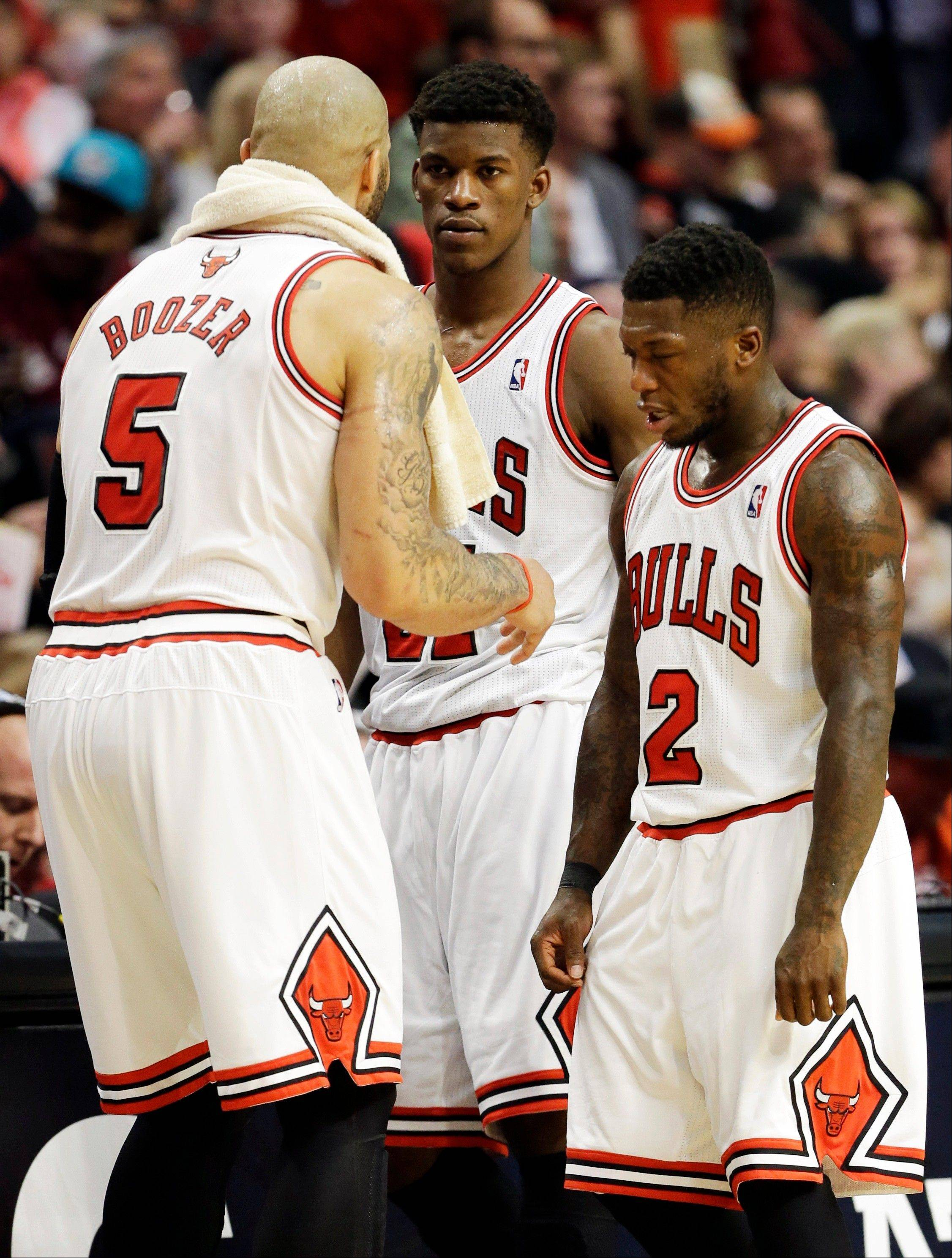 The Bulls' Carlos Boozer (5) talks to teammates Jimmy Butler (21) and Nate Robinson (2) during a timeout in the second half of the Game 5 loss to the Heat.