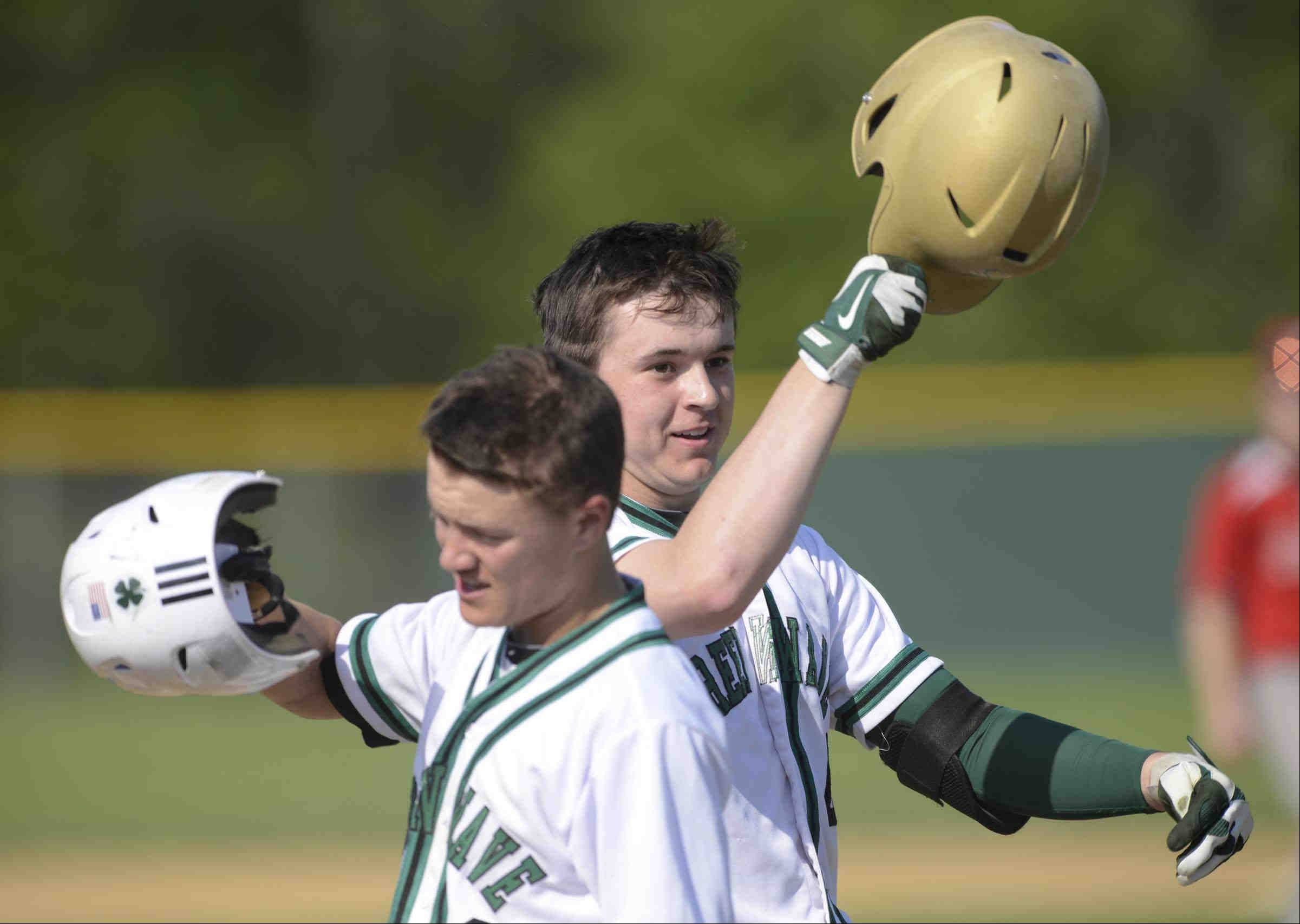 After his 2-run home run, St. Edward's Jack Tierney taps his gold helmet with teammate Michael Castoro in the first inning against Aurora Christian Thursday in the 2A Regional game in Elgin.