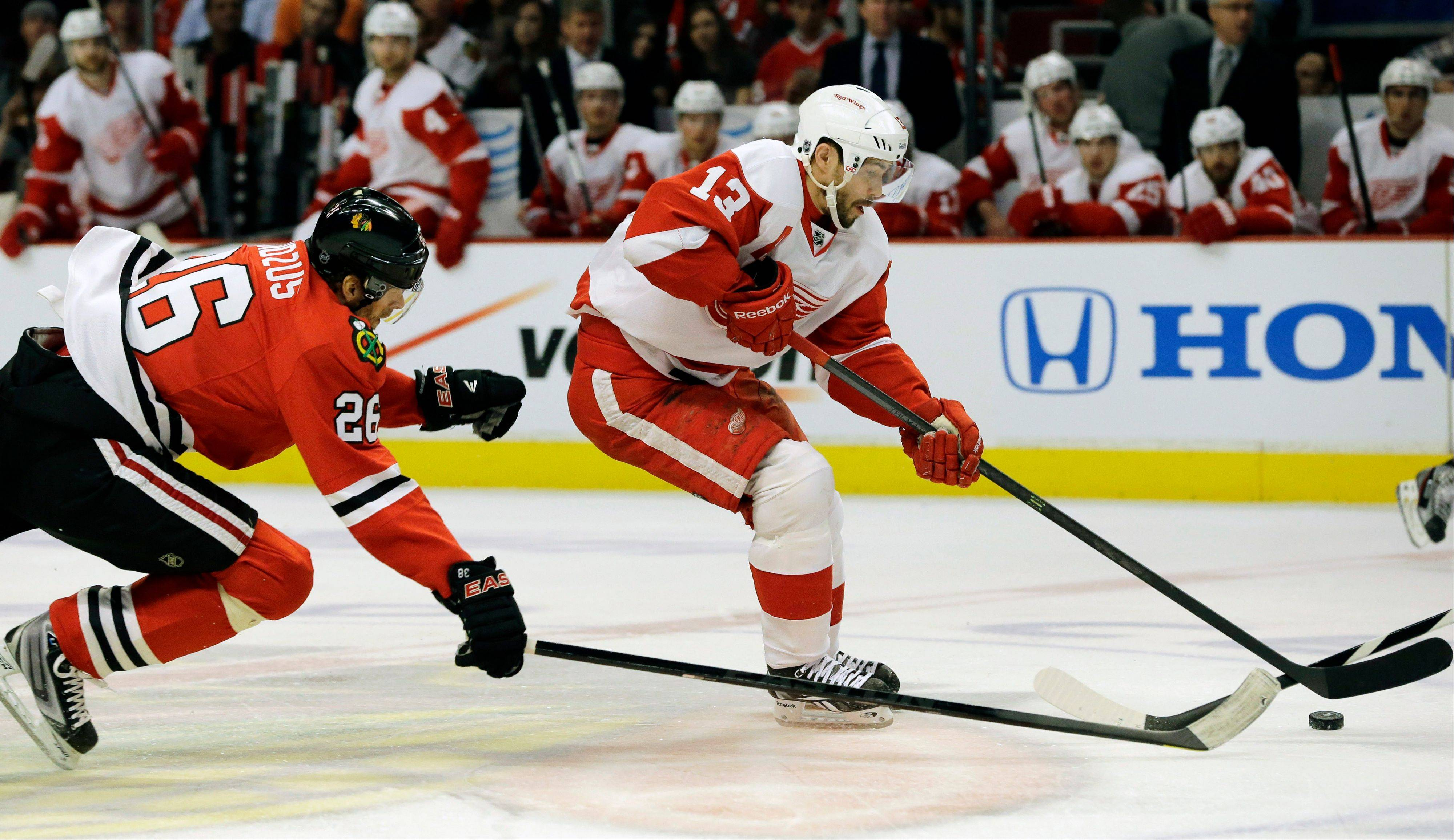 The Red Wings' Pavel Datsyuk, here controlling the puck past Michal Handzus, remains very much on the minds of the Blackhawks.