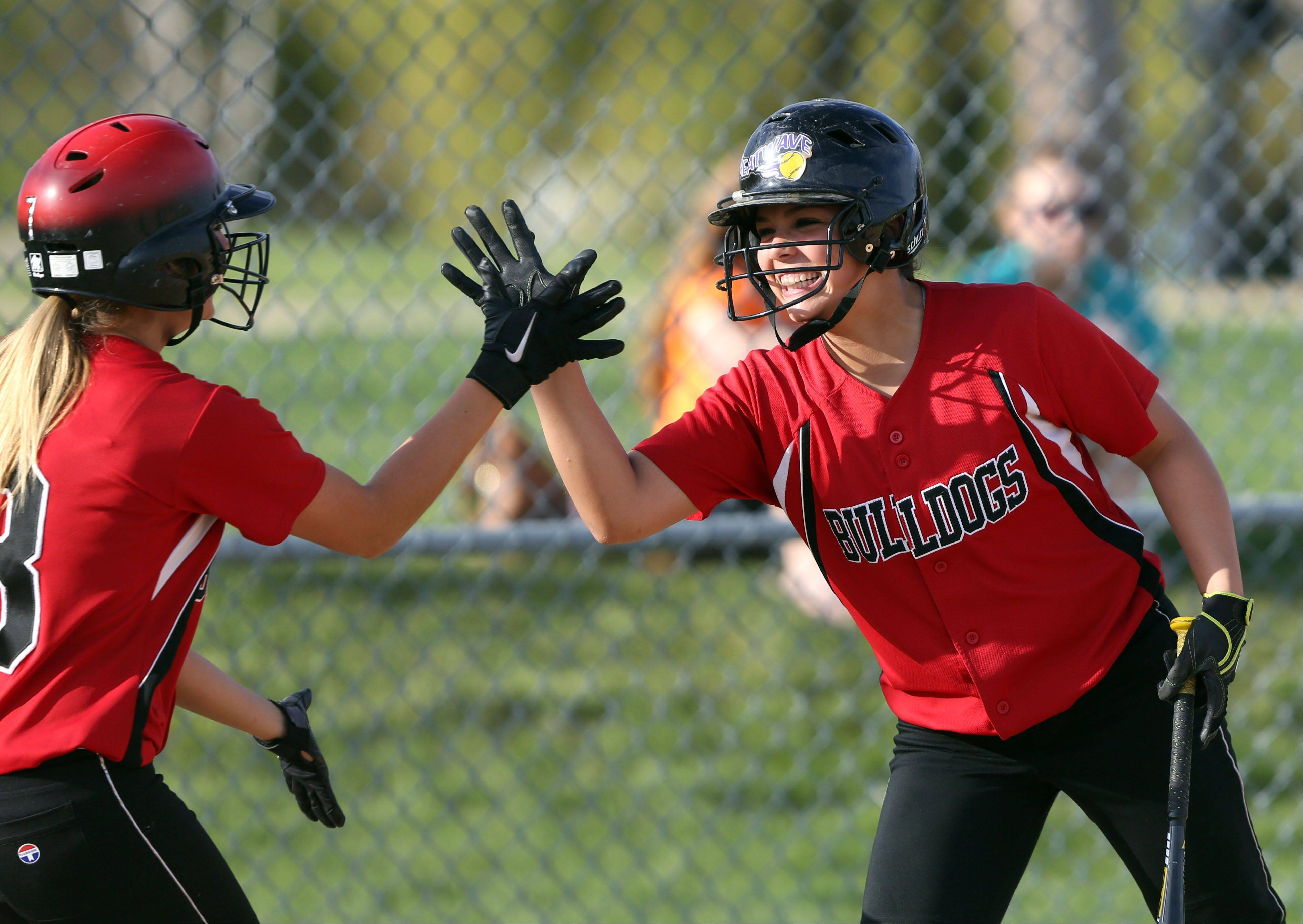Grant's Kaitlyn Wold, left, high-fives Kayla Uhwat after scoring in the fifth inning during the NSC championship game at Zion-Benton on Wednesday.
