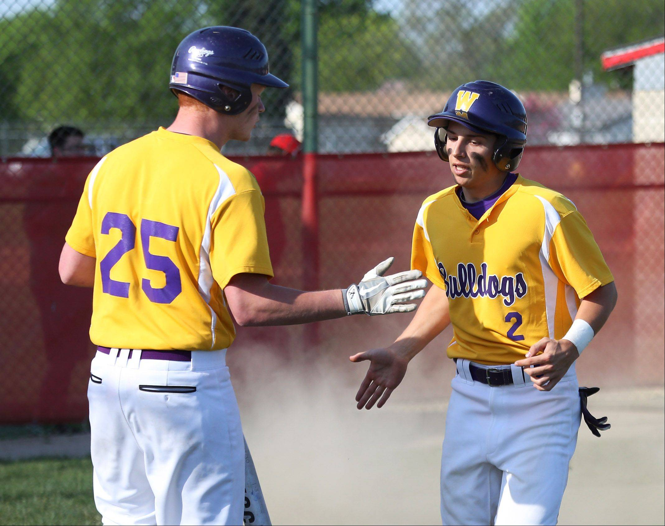 Wauconda batter Luke Kenny congratulates teammate Jeff Lindberg after he scored the first run in the fourth inning of the North Suburban Conference championship game against Mundelein on Thursday at Mundelein.