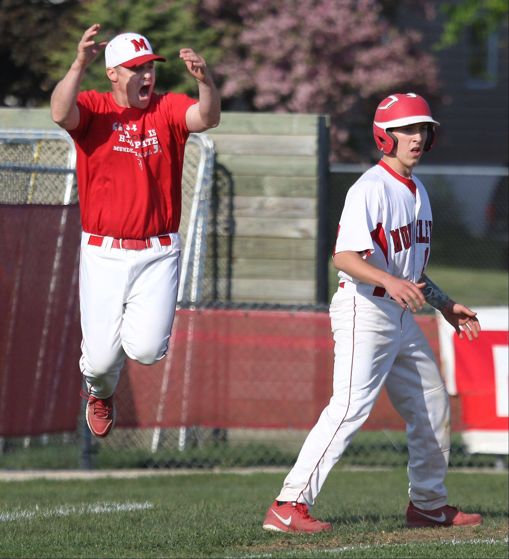 Mundelein third base coach Todd Parola can't believe the call at first base as Mundelein's Dillon O'Donoghue rounds third base during the North Suburban Conference championship game against Wauconda on Thursday at Mundelein.