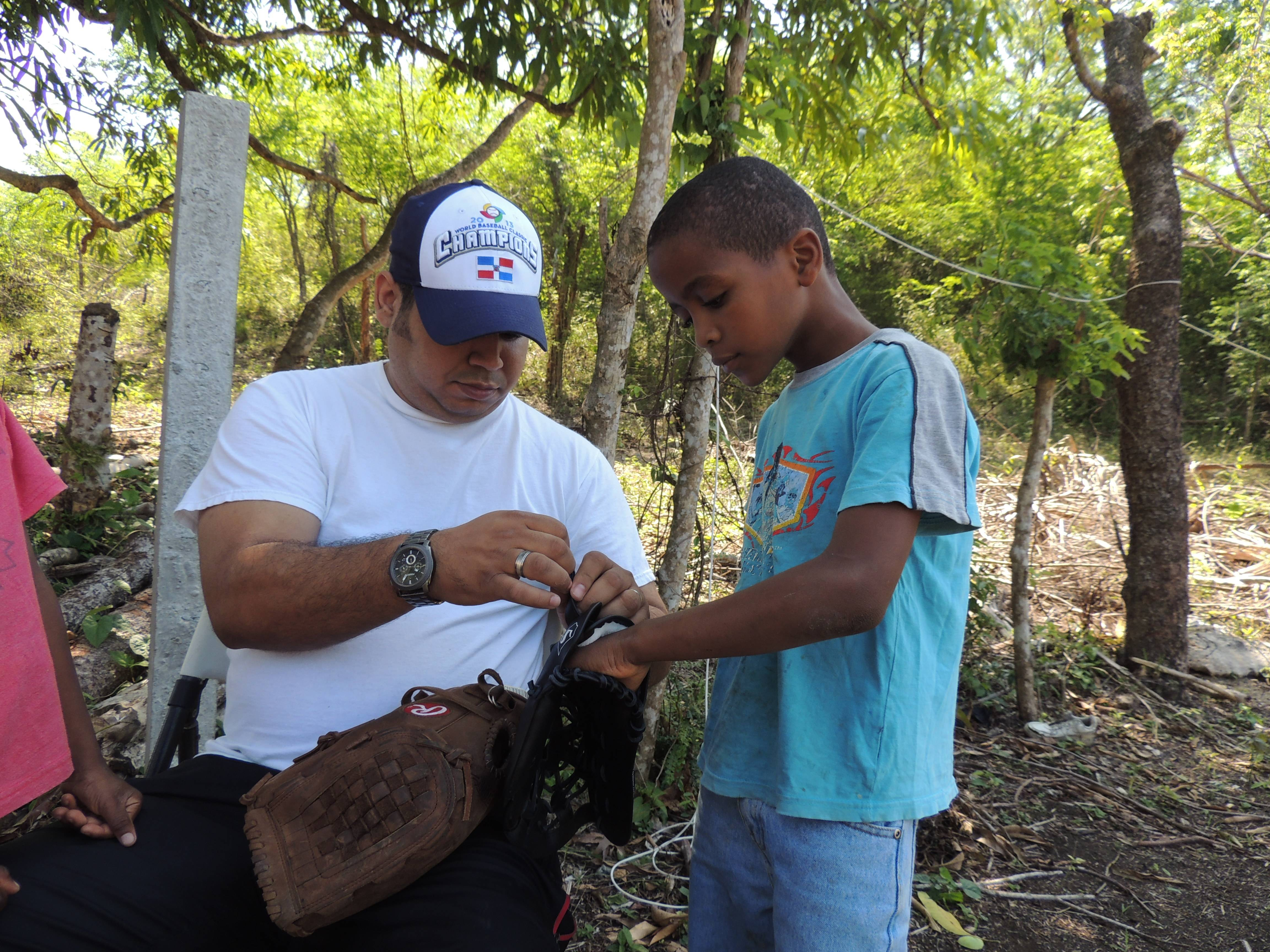 Rafael Hernandez, Country Manager for Willow Creek's relief efforts in the Dominican Republic helps a young boy fit a baseball mitt provided by charity partner Gear for Goals.