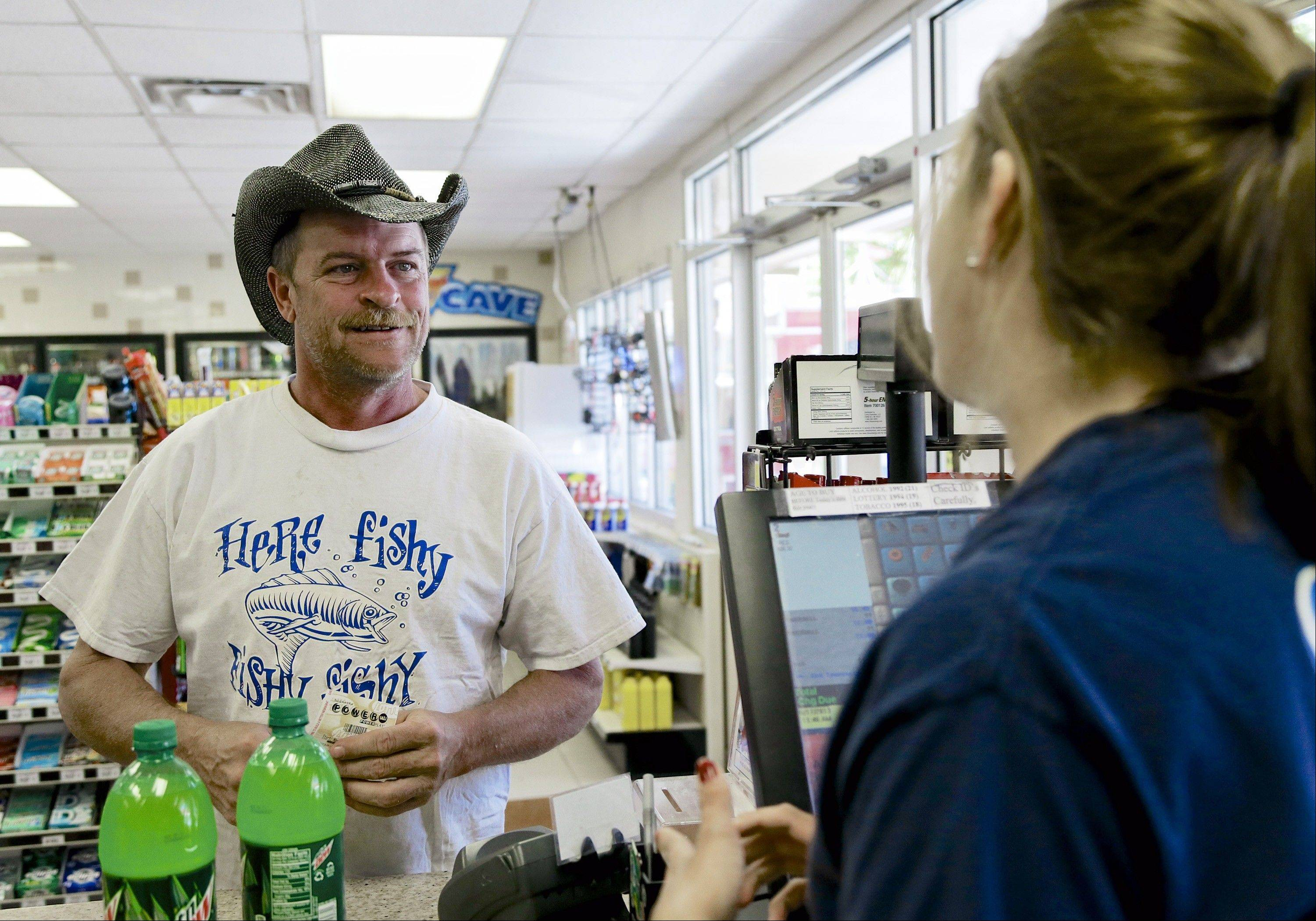 Randy Kirby of Lincoln buys a Powerball ticket Friday at a Super C convenience store in Lincoln, Neb.