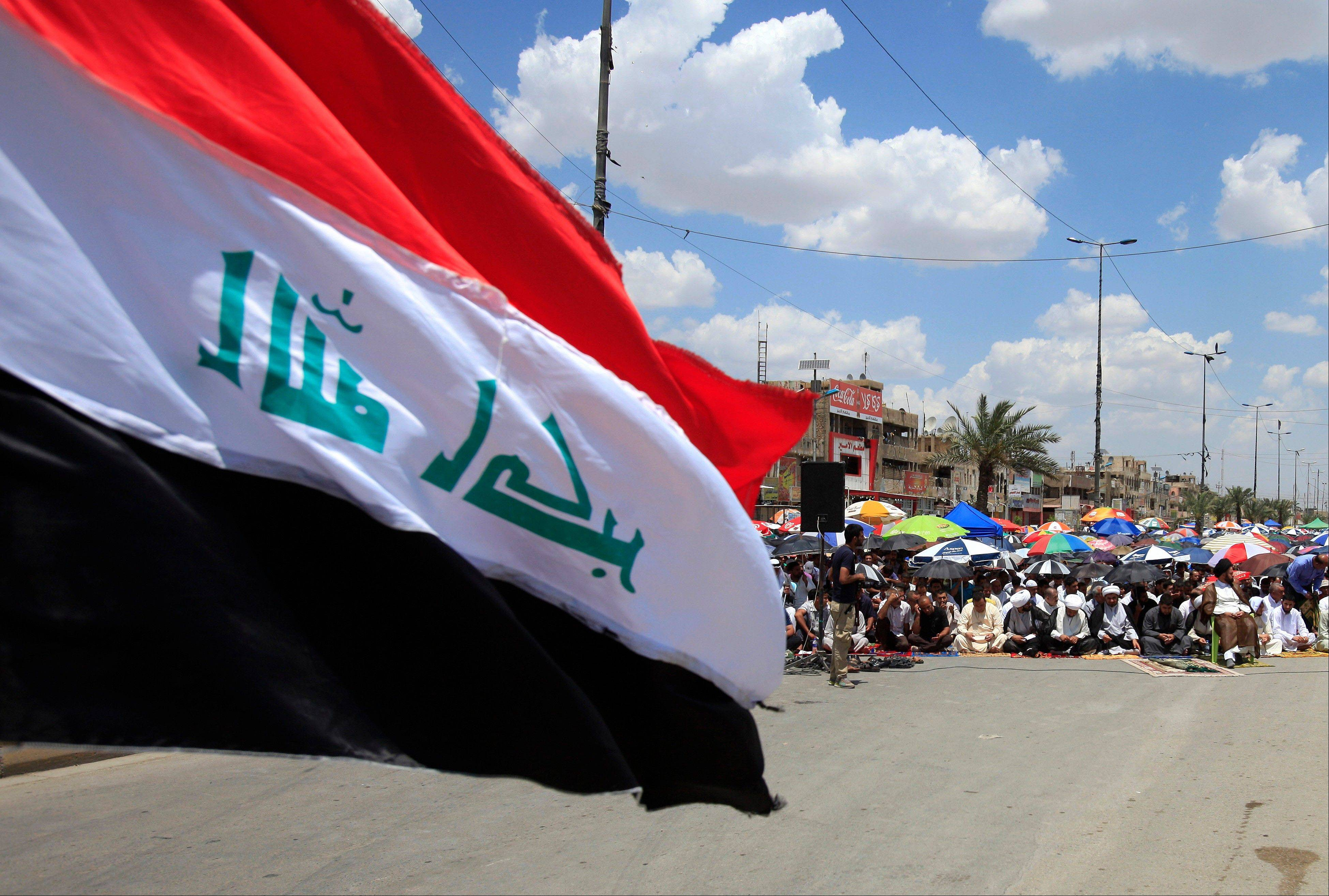 Iraq�s national flag flies as followers of radical Shiite cleric Muqtada al-Sadr attend Friday prayers in the Sadr City neighborhood in Baghdad.