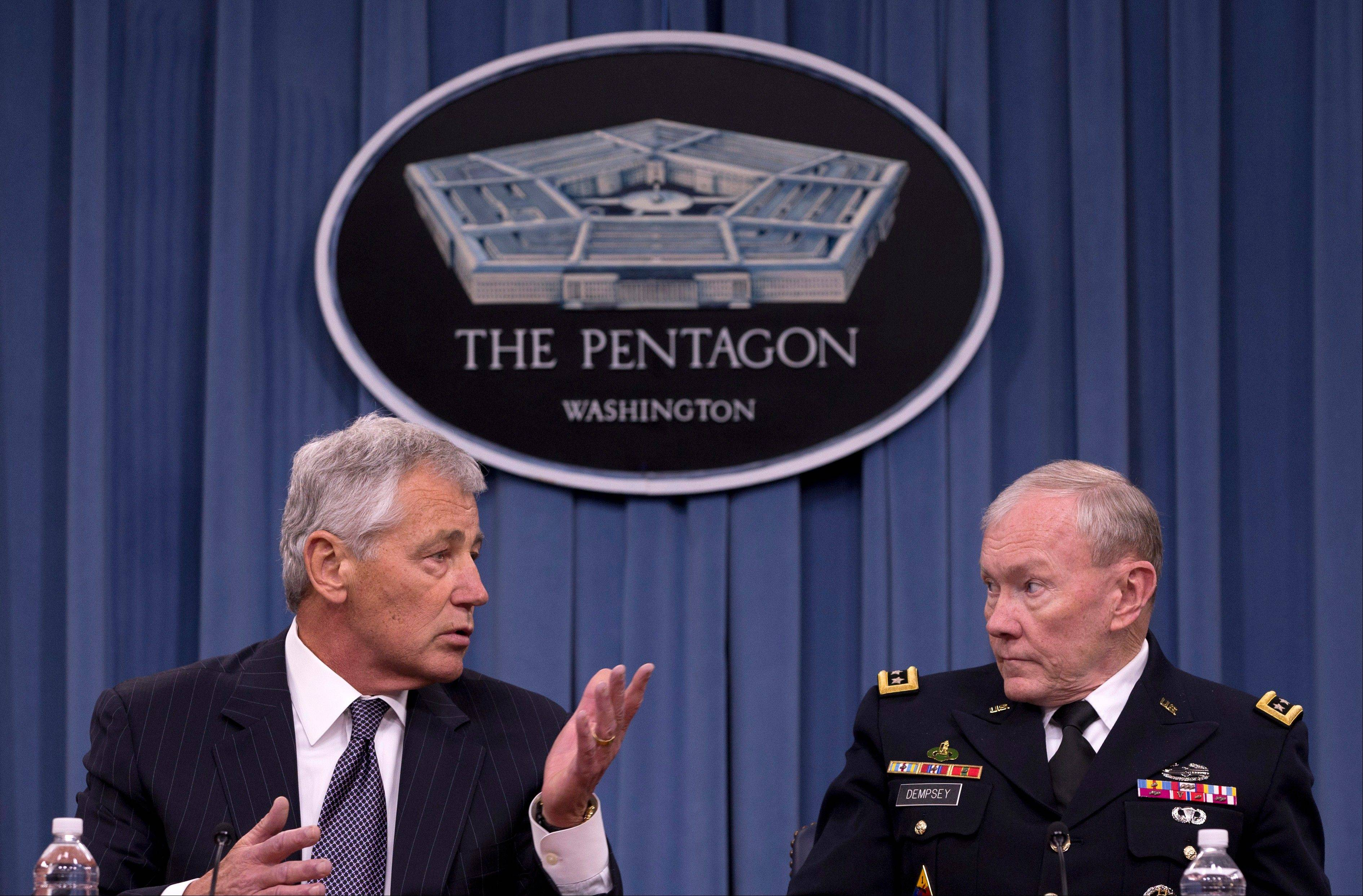 Defense Secretary Chuck Hagel, left, accompanied by Joint Chiefs Chairman Gen. Martin Dempsey, gestures Friday as he speaks during a news conference at the Pentagon.