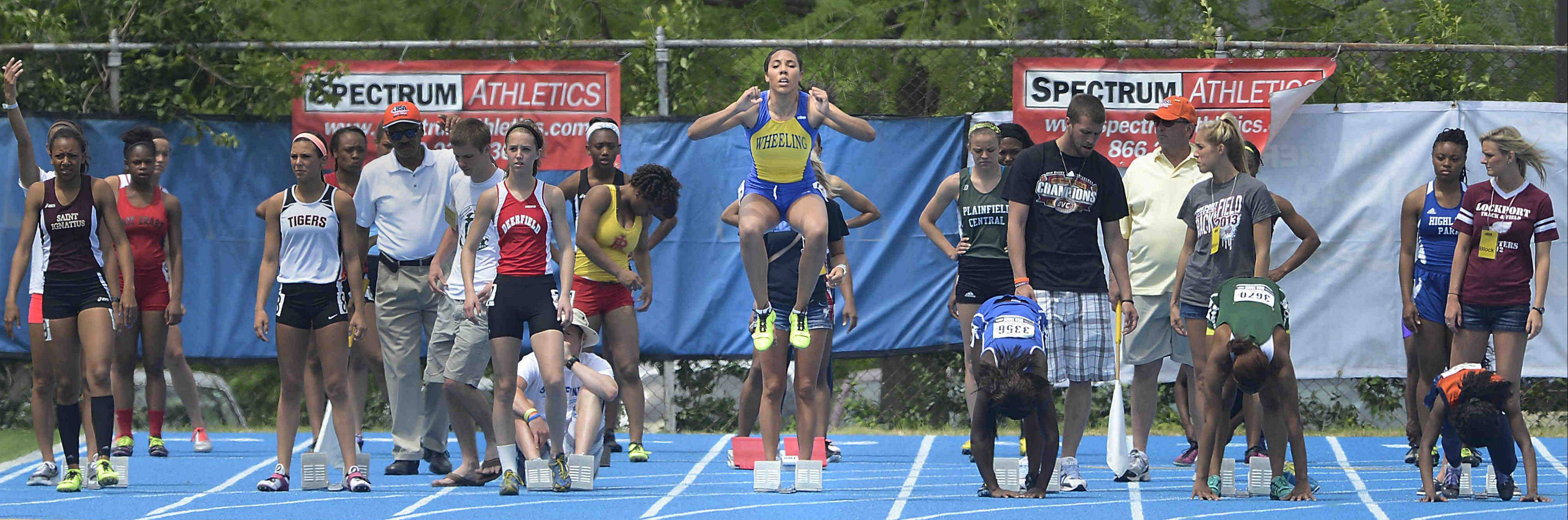 As the other competitors step into their starting blocks for the 100-meter dash, Wheeling's Sydney Keith jumps up Friday at the Class 3A girls state track and field preliminaries at Eastern Illinois University.