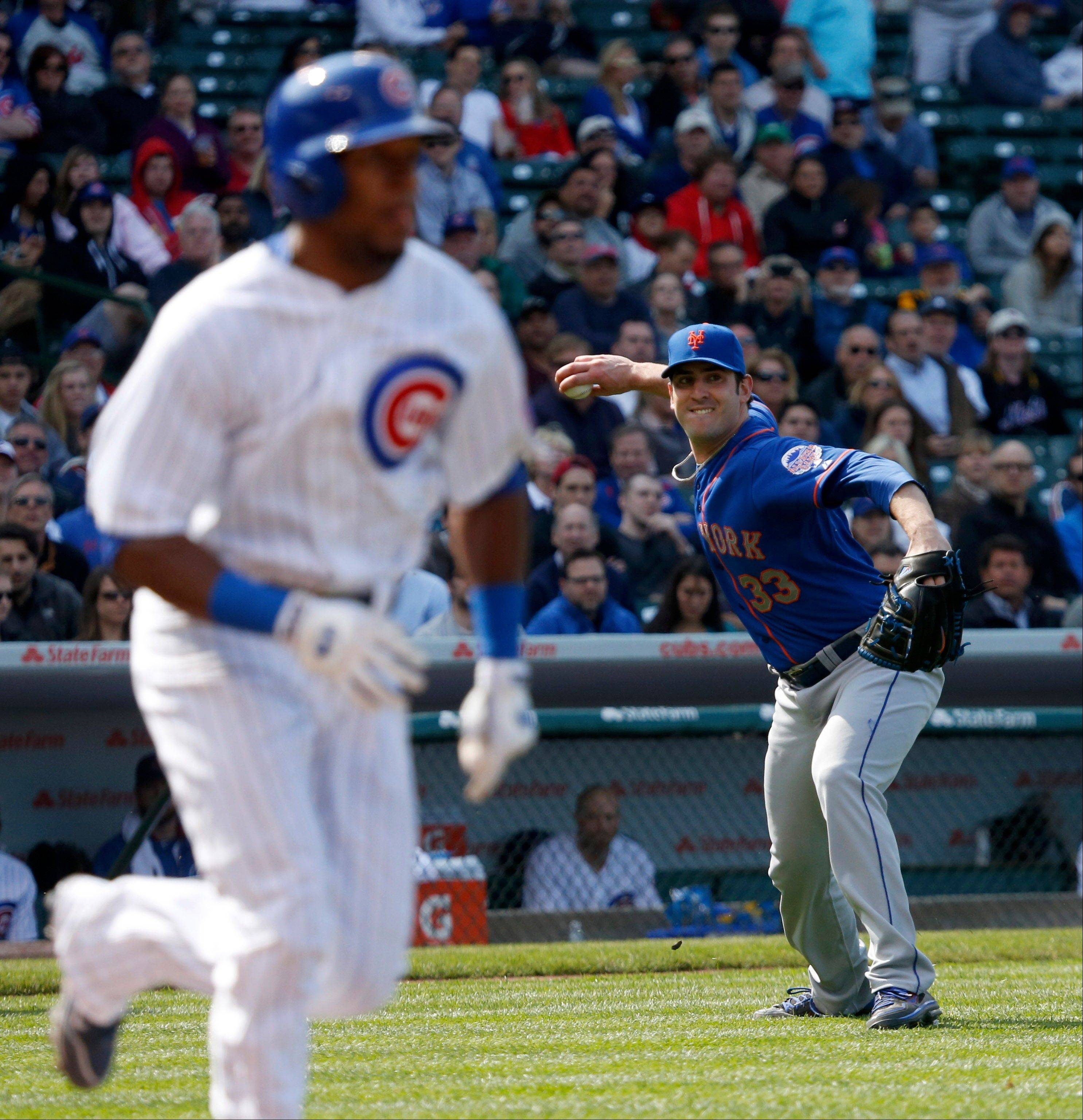 New York Mets starting pitcher Matt Harvey, right, fields a bunt by Chicago Cubs pinch hitter Julio Borbon and throws him out at first during the eighth inning of a baseball game Friday, May 17 2013, in Chicago. (AP Photo/Charles Rex Arbogast)