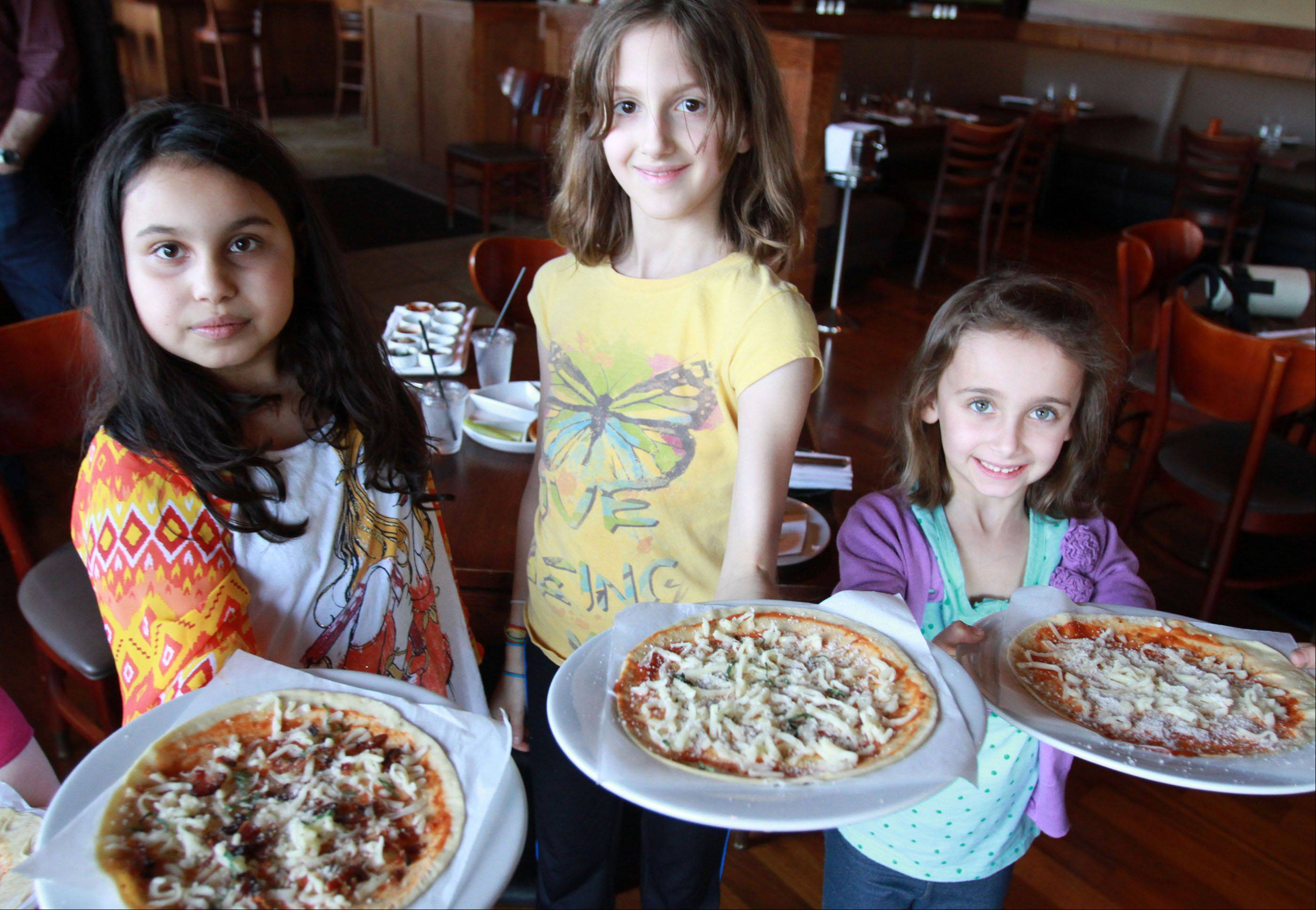 Jaya Nambiar, 9, from left, Kaya Booth, 9, both of Wilmette, and Helena Samson, 6, of Northbrook show healthy pizzas they made for themselves at Prairie Grass Cafe in Northbrook on Friday, April 26. The pizza making was hosted by Sarah Stegner, co-chef and co-owner, w