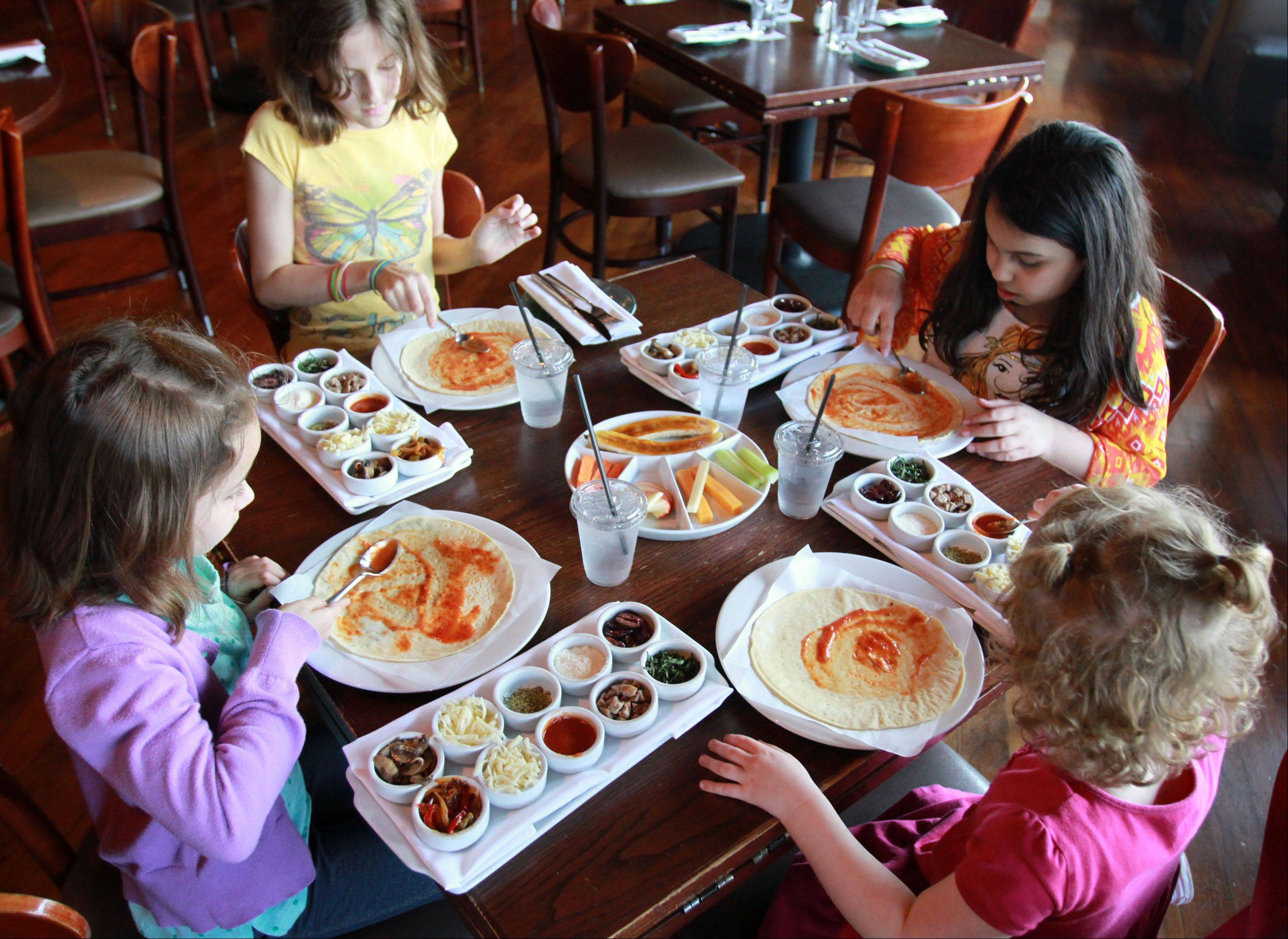 "Helena Samson, 6, of Northbrook, at left then clockwise, Kaya Booth, 9, Jaya Nambiar, 9, both of Wilmette, and Olicia Samson, 3, of Northbrook make healthy pizzas for themselves at Prairie Grass Cafe in Northbrook on Friday, April 26. The pizza making was hosted by Sarah Stegner, co-chef and co-owner, who is one of the founding members of the ""Healthy Fare for Kids"" initiative, which encourages restaurants to offer healthier food for children."