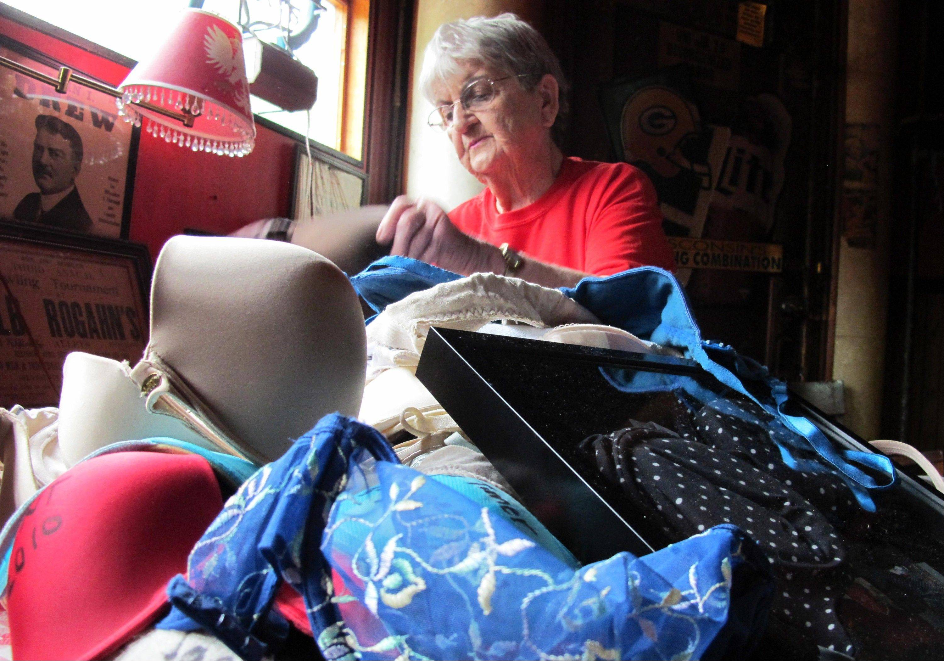 Marcy Skowronski, 87, looks through a pile of bras Friday that used hang from the ceiling of her bar, Holler House, in Milwaukee.