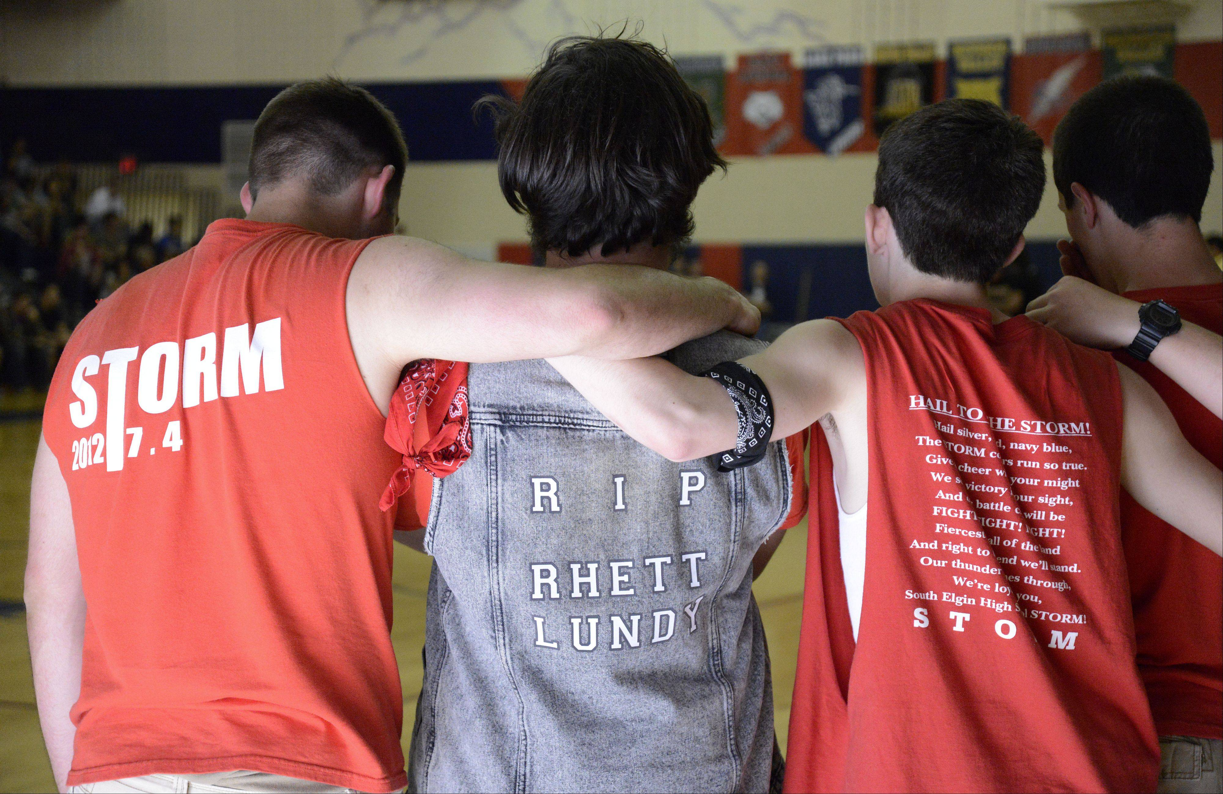 South Elgin High School drum line members, from left, senior Matt Dalbke, junior Peter Brankovic and sophomore Chandler Carrico embrace Friday following their tribute performance to fellow drummer Rhett Lundy, a freshman who died in his sleep Wednesday.