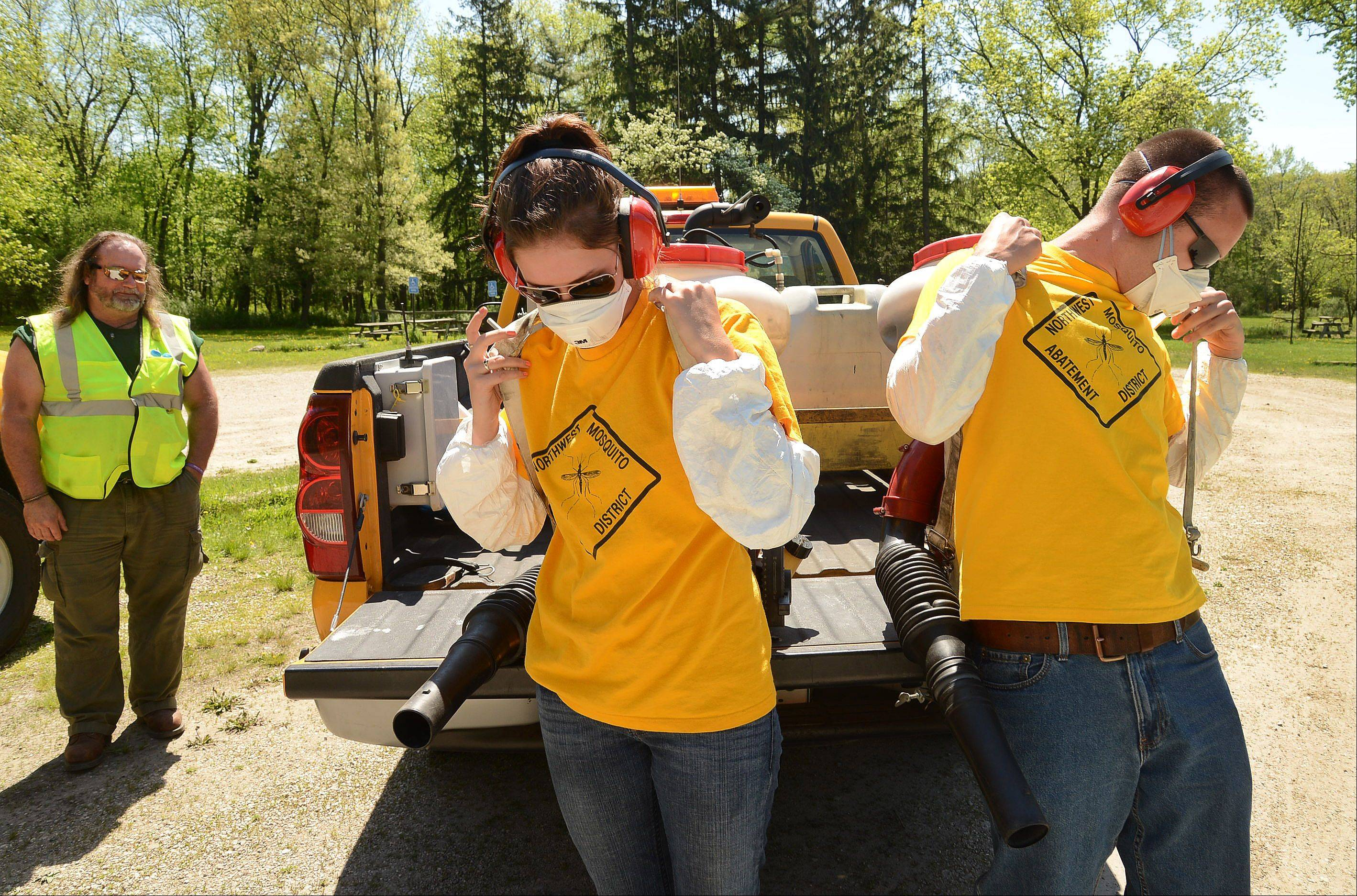 Northwest Mosquito Abatement District Field Technicians Shannon Stutzman and Kevin Ollerer strap on their backpacks to perform mosquito abatement in the Potawatomi Woods Forest Preserve near Wheeling under the direction of Chief of Field Operations Mark Baker, left.