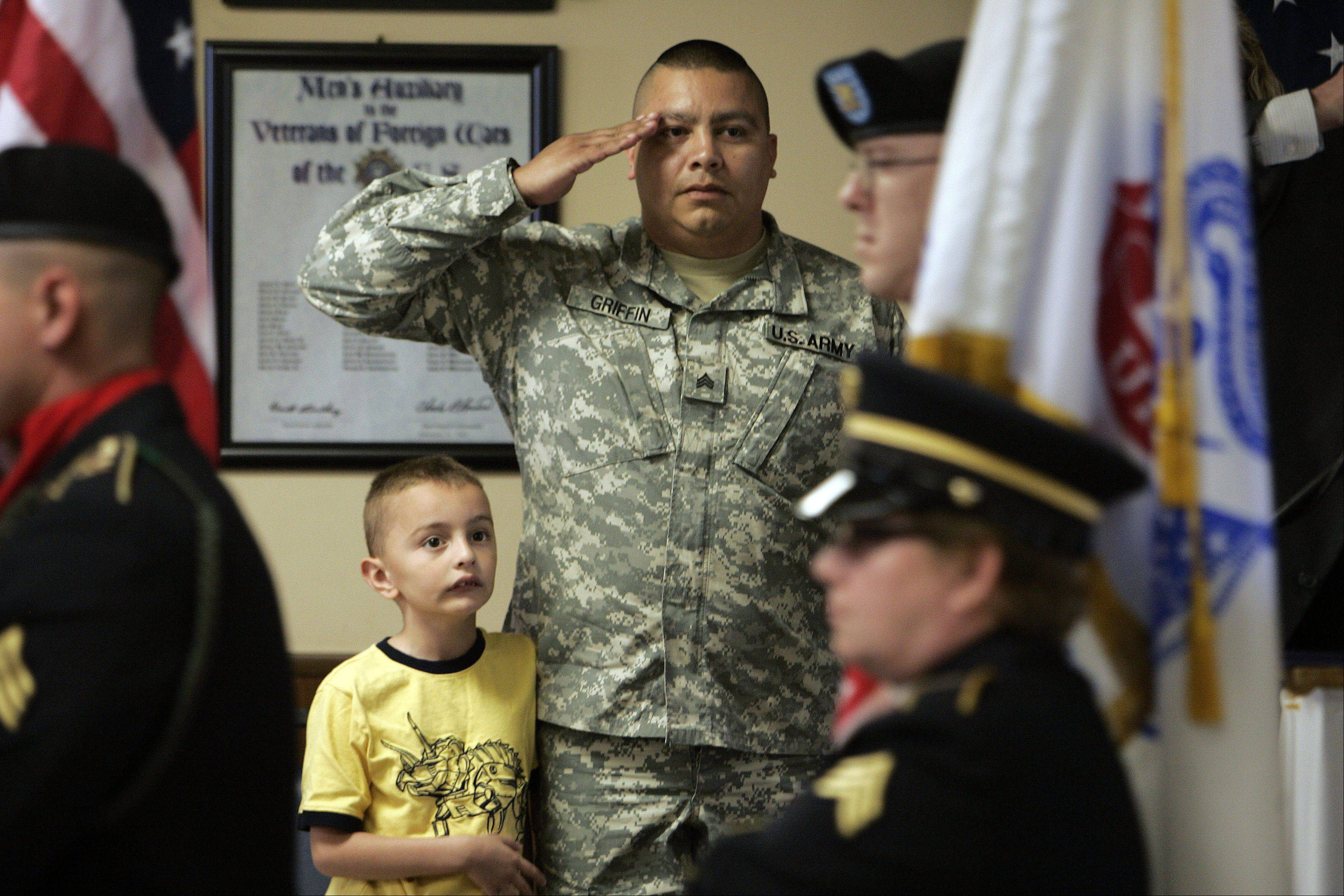 Retired U.S. Army Sgt. Michael Griffin and his son Michael Griffin II, 6, stand and salute as the colors are presented by an Honor Guard.