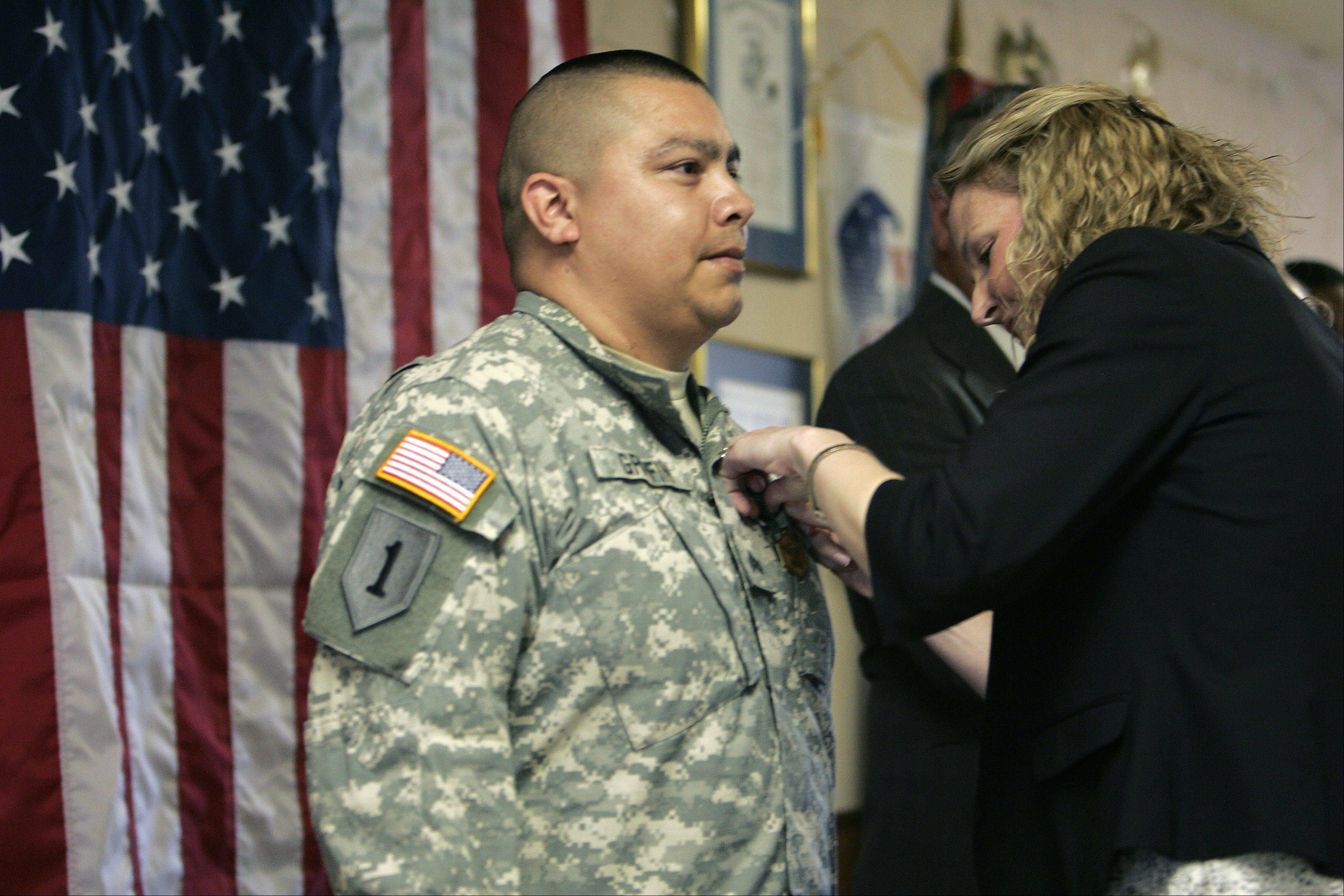 Retired U.S. Army Sgt. Michael Griffin of Carpentersville receives the Army Commendation Medal of Valor from Erica Borggren, director of Illinois Department of Veterans' Affairs.